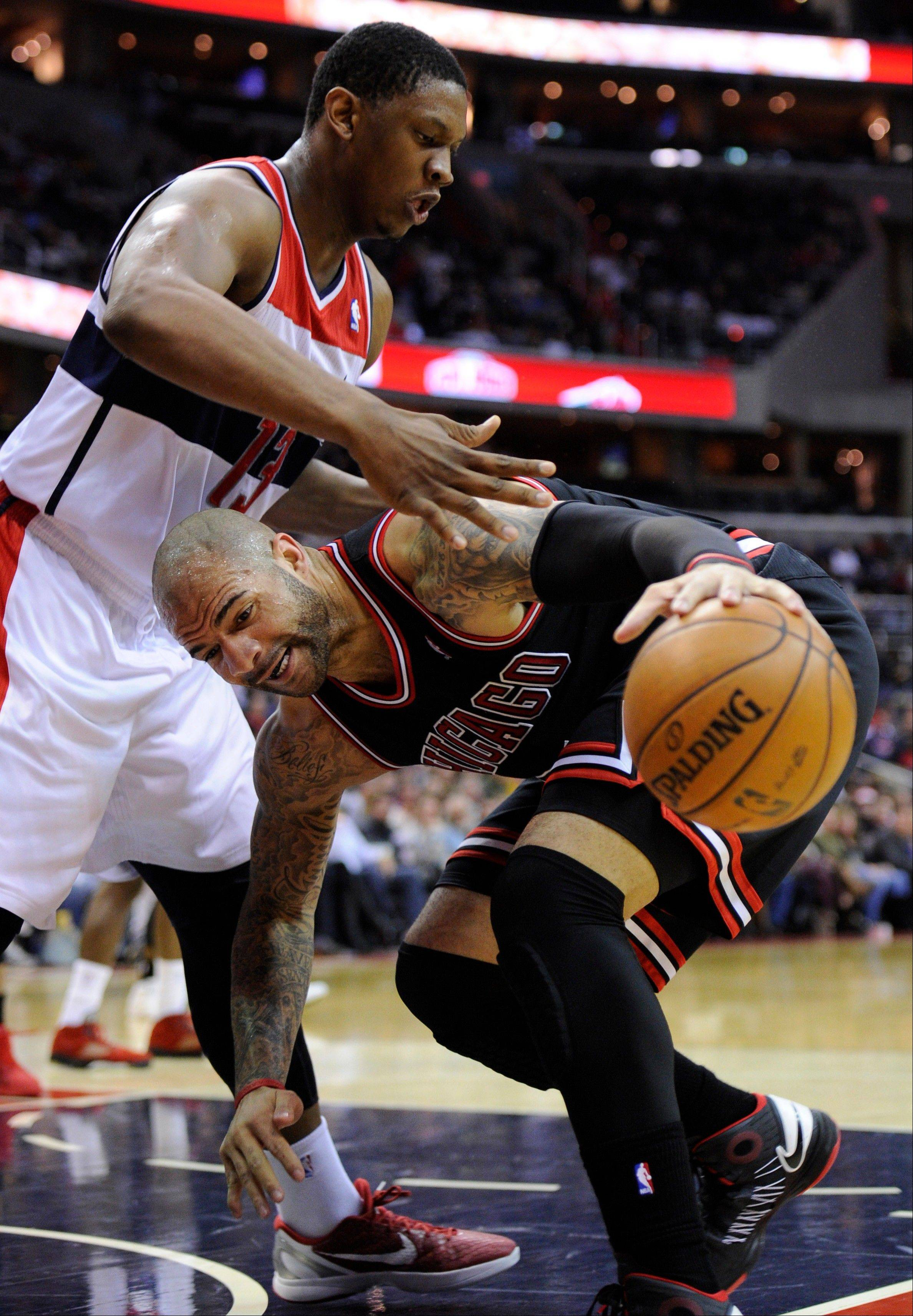 Chicago Bulls forward Carlos Boozer, right, drives to the basket against Washington Wizards forward Kevin Seraphin (13) during the first half of an NBA basketball game, Saturday, Jan. 26, 2013, in Washington.