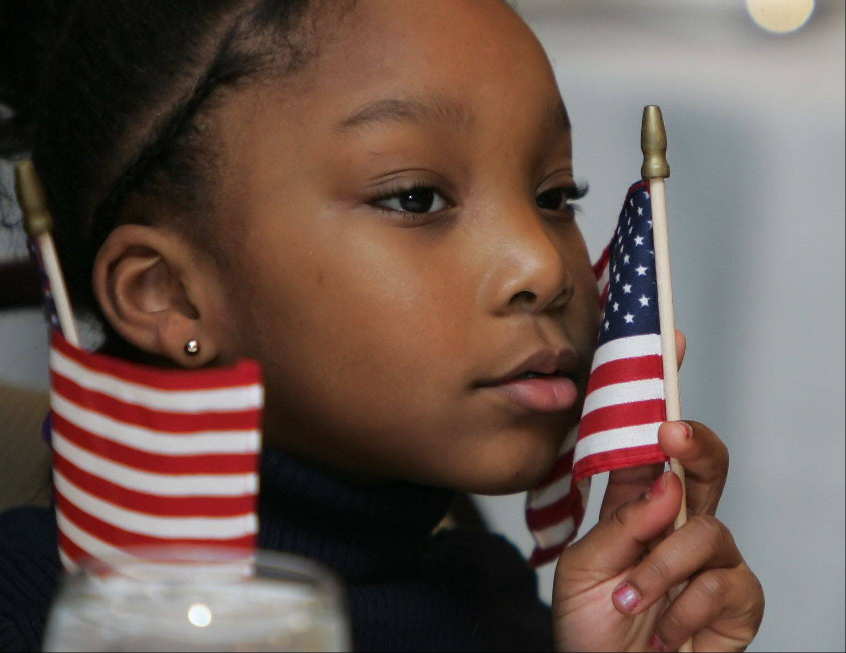 Six-year-old Makayla Bowles, of Zion, holds a flag as she watches the President Barack Obama Inauguration event Monday at the Holiday Inn - Gurnee Convention Center. Several large-screen televisions were in place for people to watch the inauguration sponsored by the Black Chamber of Commerce of Lake County.