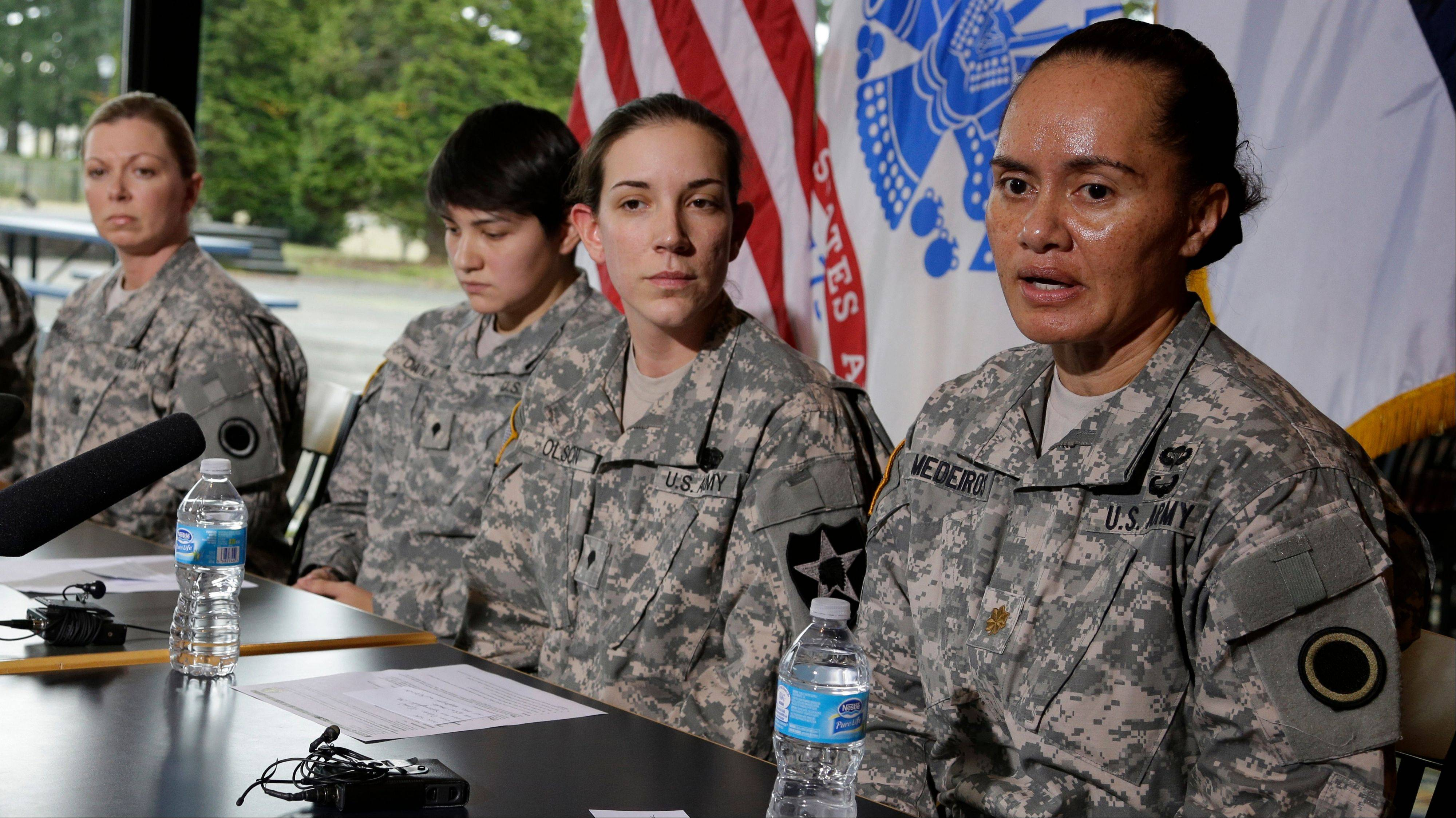 U.S. Army soldiers, from left, 1st Sgt. Marcia McGee, Spc. Vanessa Davila, Spc. Heidi Olson and Maj. Sheila Medeiros talk to reporters Thursday at Joint Base Lewis McChord, Wash., about the decision announced by defense leaders Thursday to open a quarter-million combat and other military positions to service members regardless of gender.