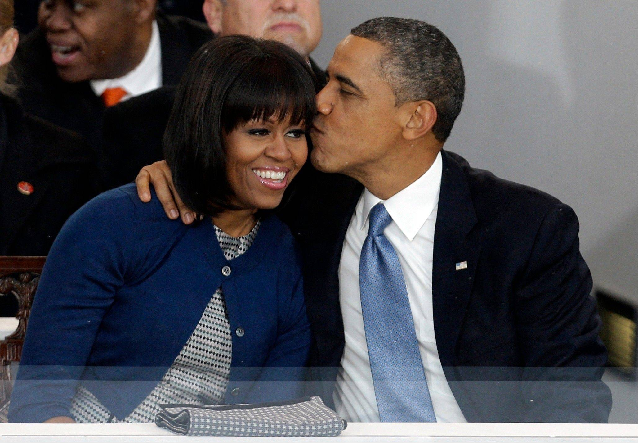 President Barack Obama kisses first lady Michelle Obama in the presidential box near the White House as bands march past the presidential box Monday during inauguration parade.