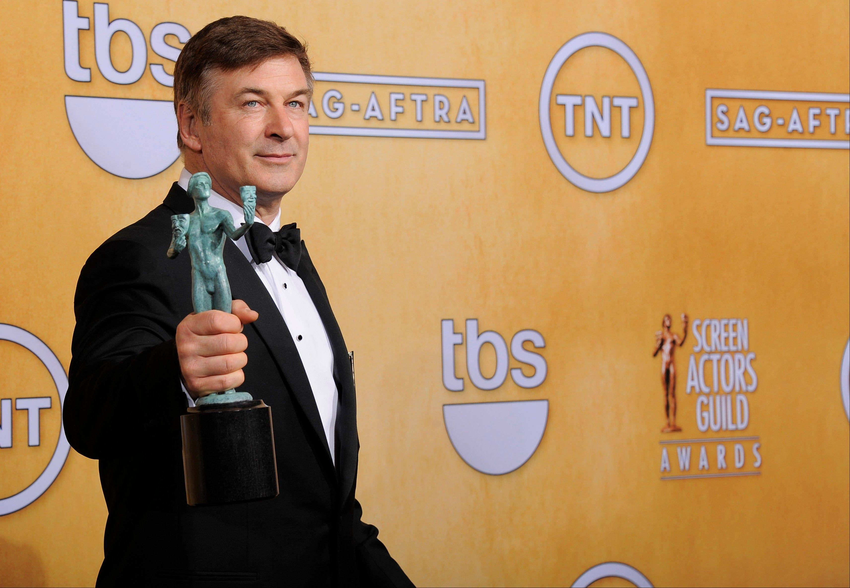 Actor Alec Baldwin poses backstage with the award for best male actor in a comedy series at the 19th Annual Screen Actors Guild Awards at the Shrine Auditorium in Los Angeles on Sunday Jan. 27, 2013.