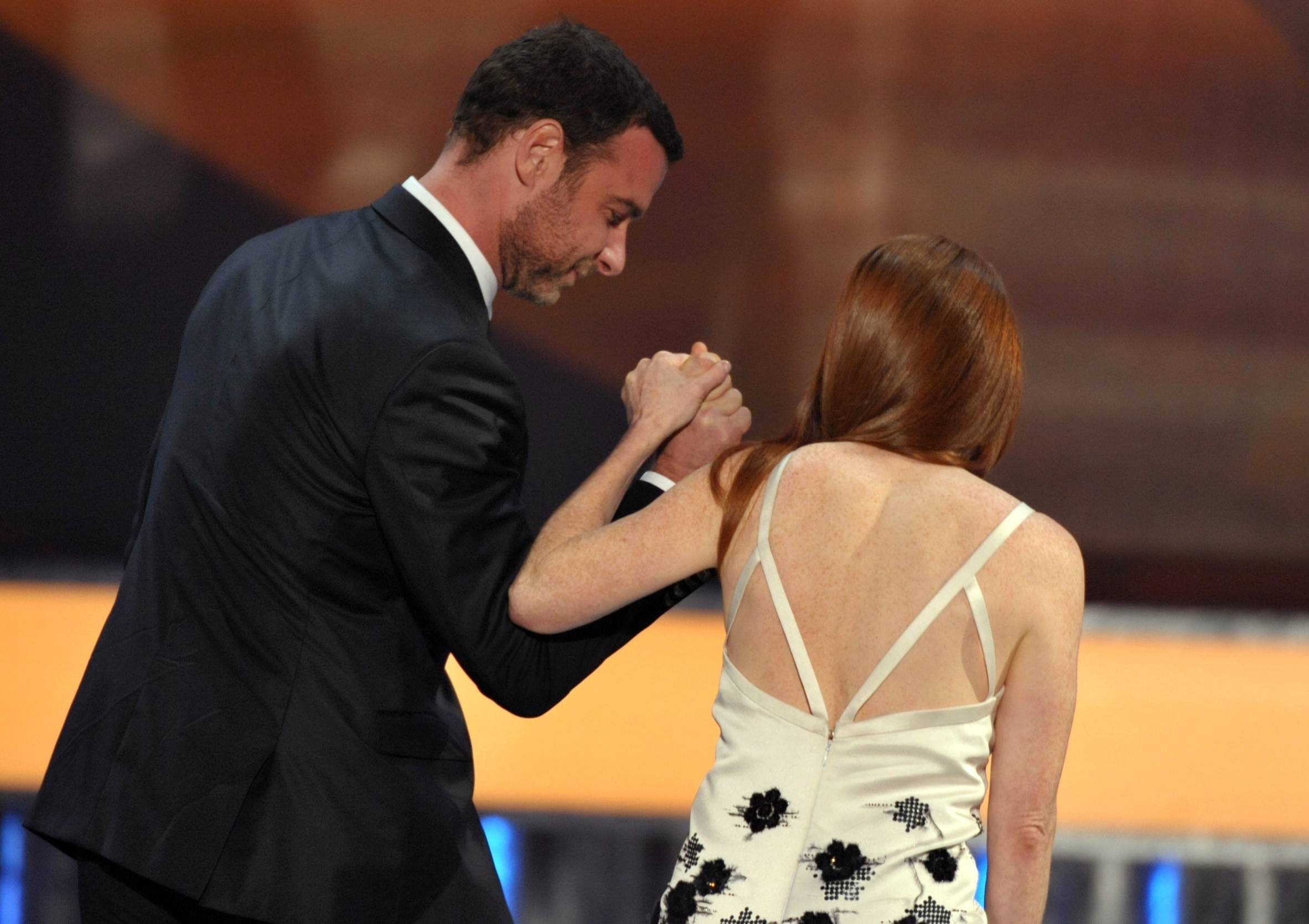 "Liev Schrieber helps Julianne Moore onto the stage after she was announced the winner for her role in ""Game Change."""