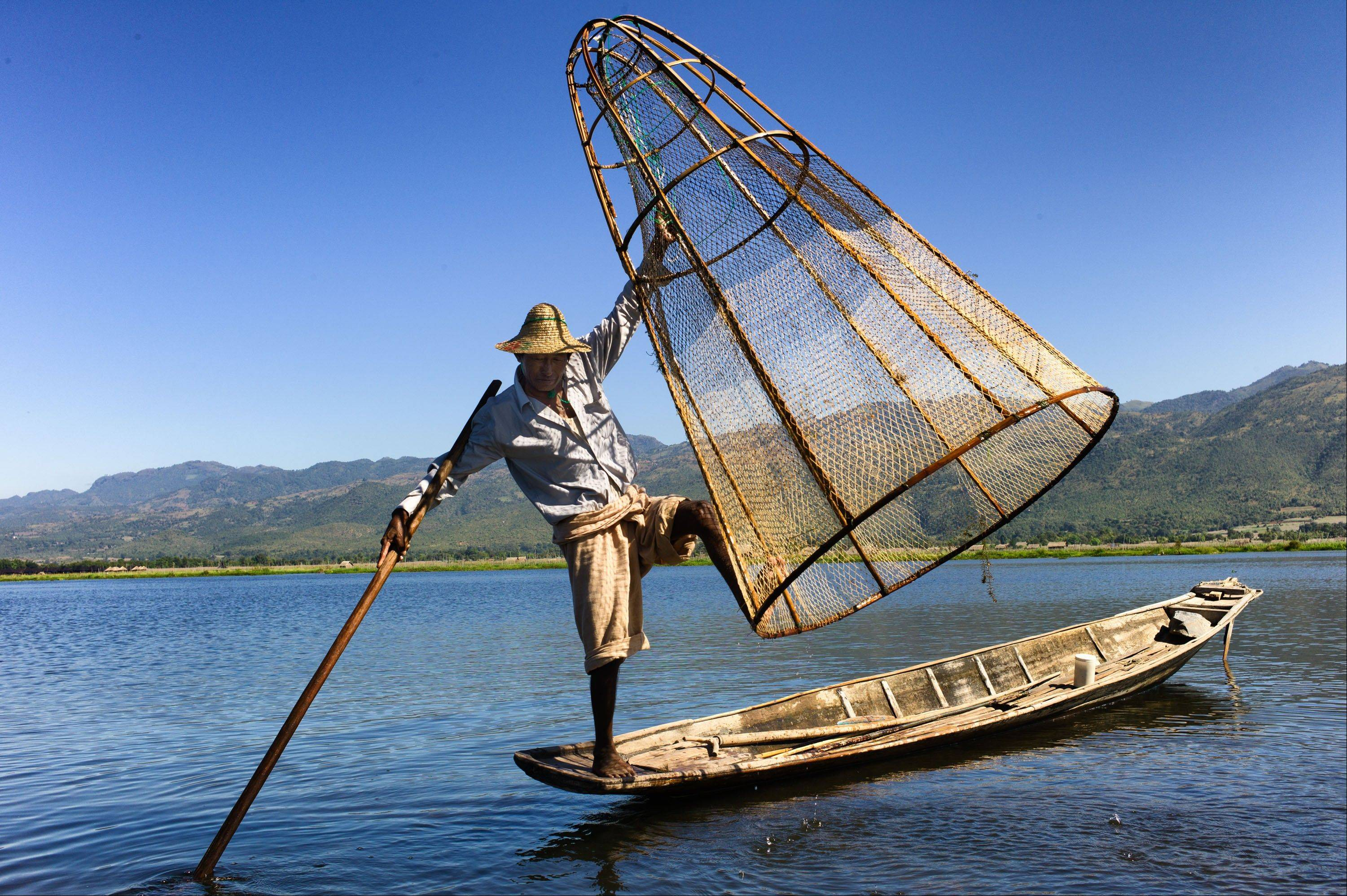 A fisherman balances his boat, net and oar in Inle Lake, a picturesque area of Myanmar that is popular with tourists.