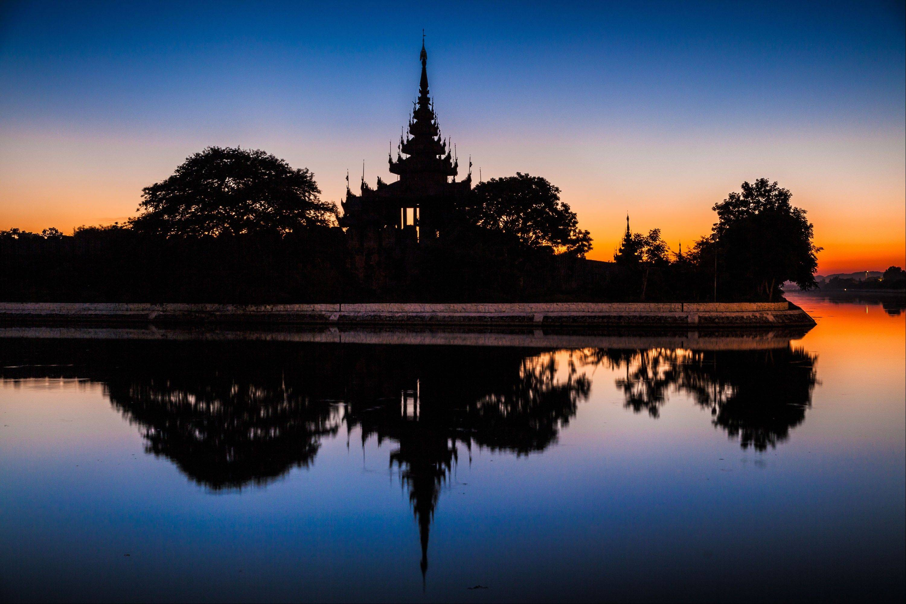 Mandalay Palace is reflected in a surrounding moat in Mandalay.