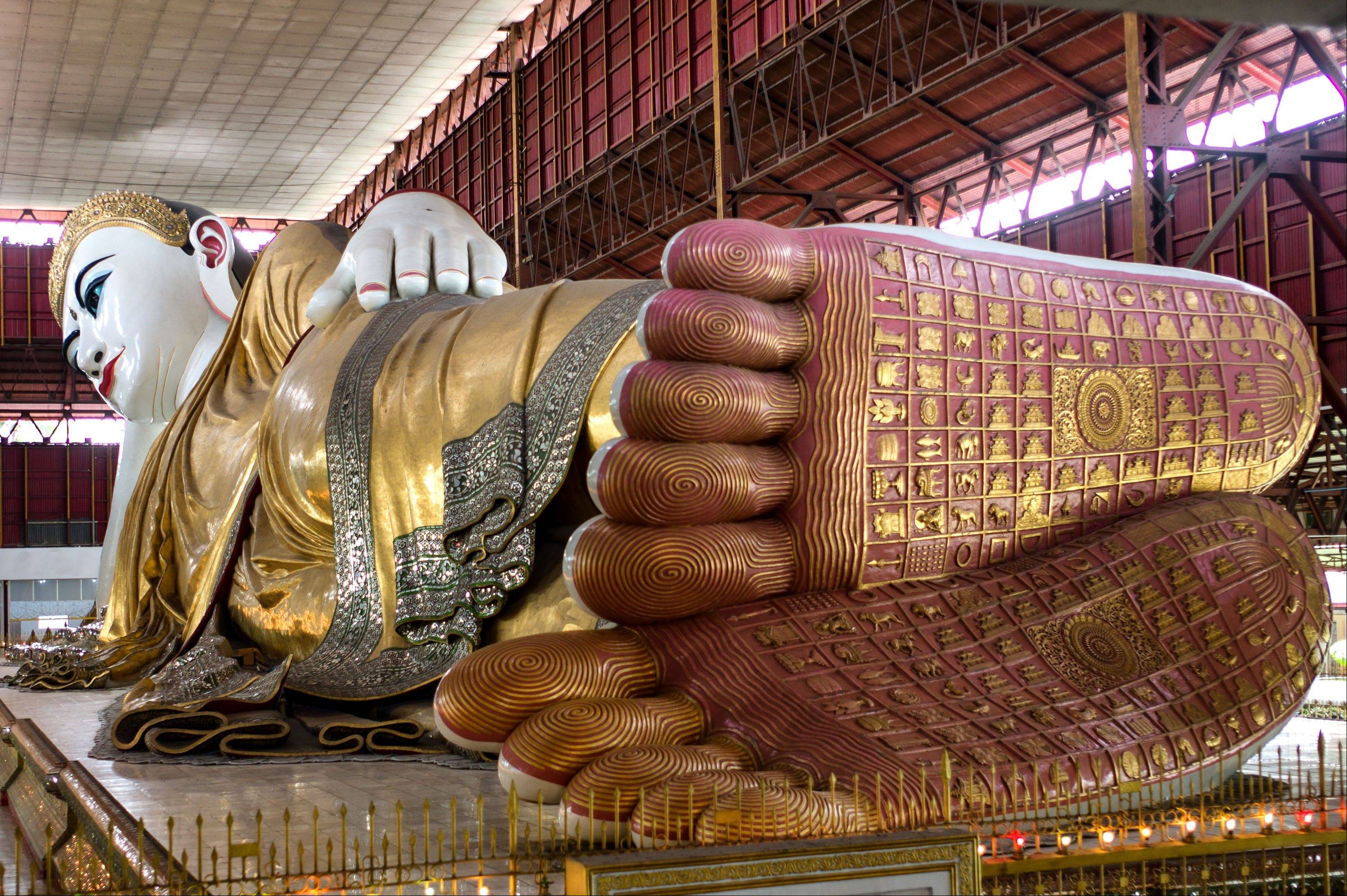 A reclining Buddha is decorated in gold leaf at the Chaykhtatgyi Pagoda in Mandalay.