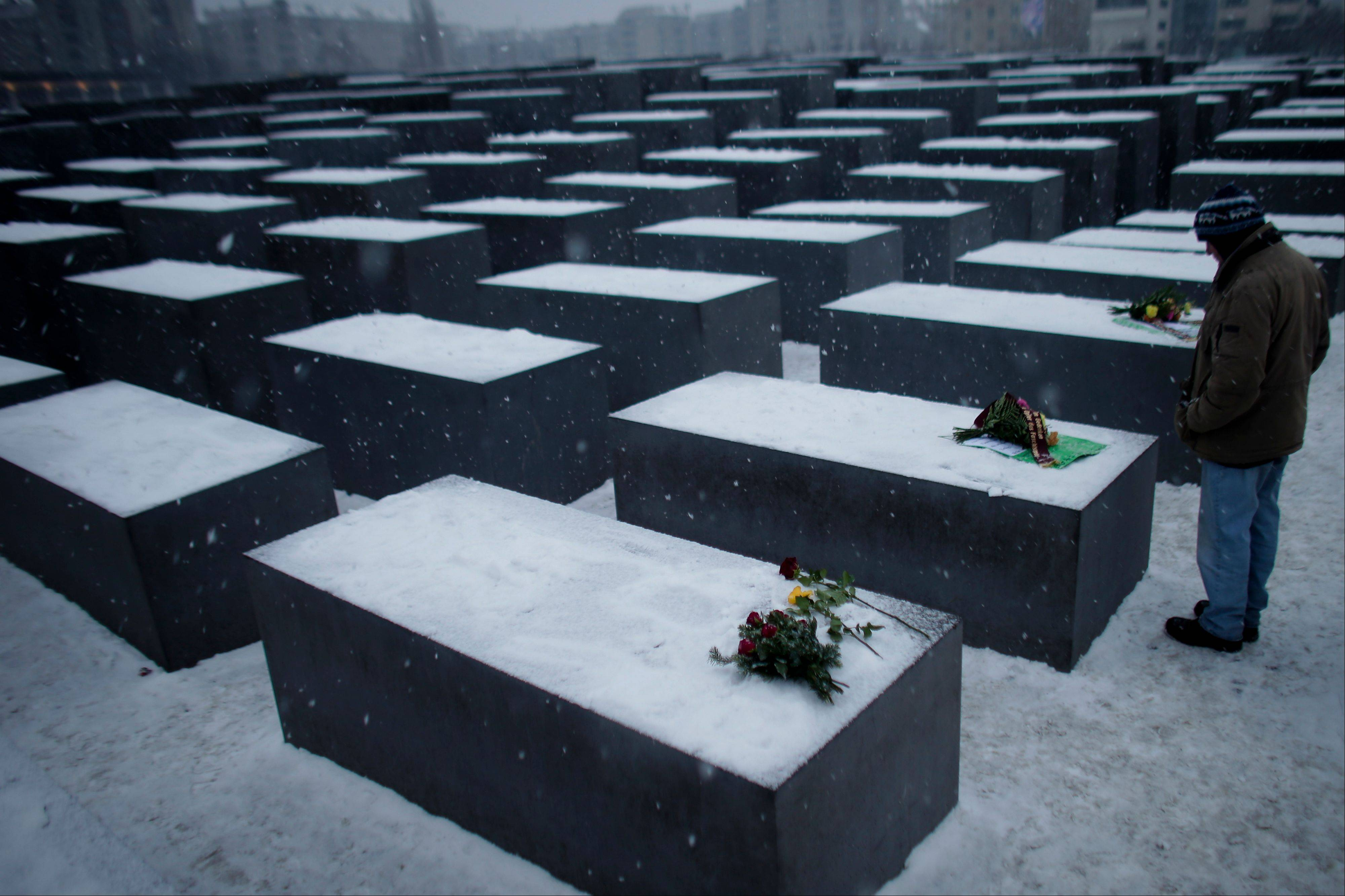 A man stands next to flowers on slabs of the Holocaust Memorial to commemorate the victims of the Nazi regime at the International Holocaust Remembrance Day in Berlin Sunday. The International Holocaust Remembrance Day marks the liberation of the Auschwitz death camp on Jan. 27, 1945.