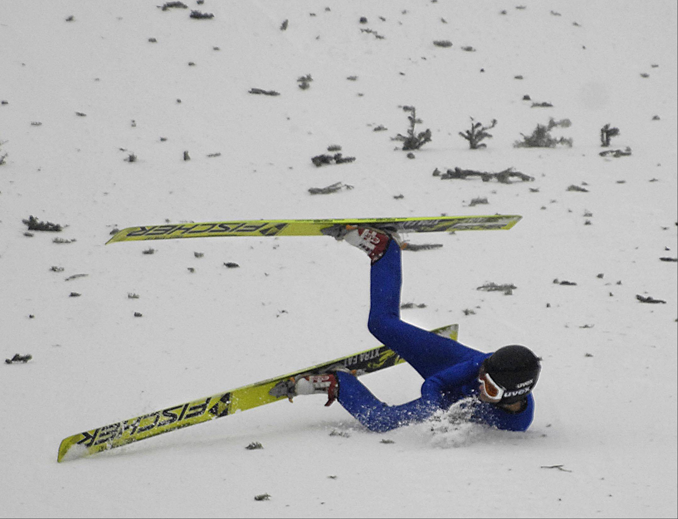 Rolf Ole Sommerstad, of Norway, tumbles to a stop after falling on his landing Sunday at the 108th Annual International Ski Jumping Tournament at Norge Ski Club in Fox River Grove. The pieces of pine trees are stuck in the snow to give depth and dimension to help the jumpers locate the ground.