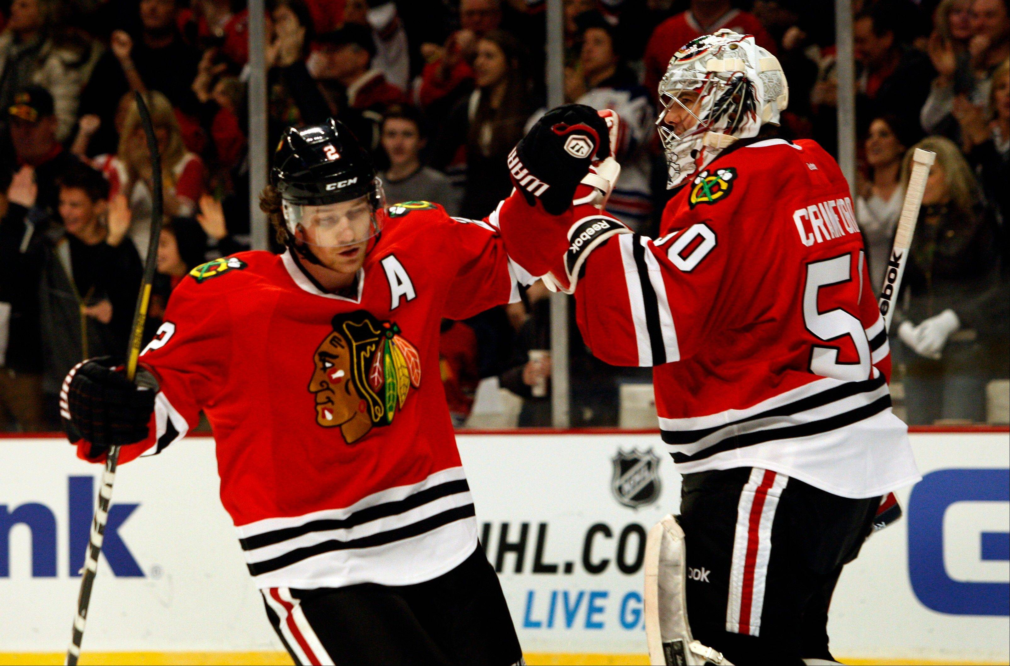 Duncan Keith, left, is congratulated by Blackhawks goalie Corey Crawford in the first period after Keith scored against the Detroit Red Wings during an NHL hockey game in Chicago, Sunday, Jan. 27, 2013.