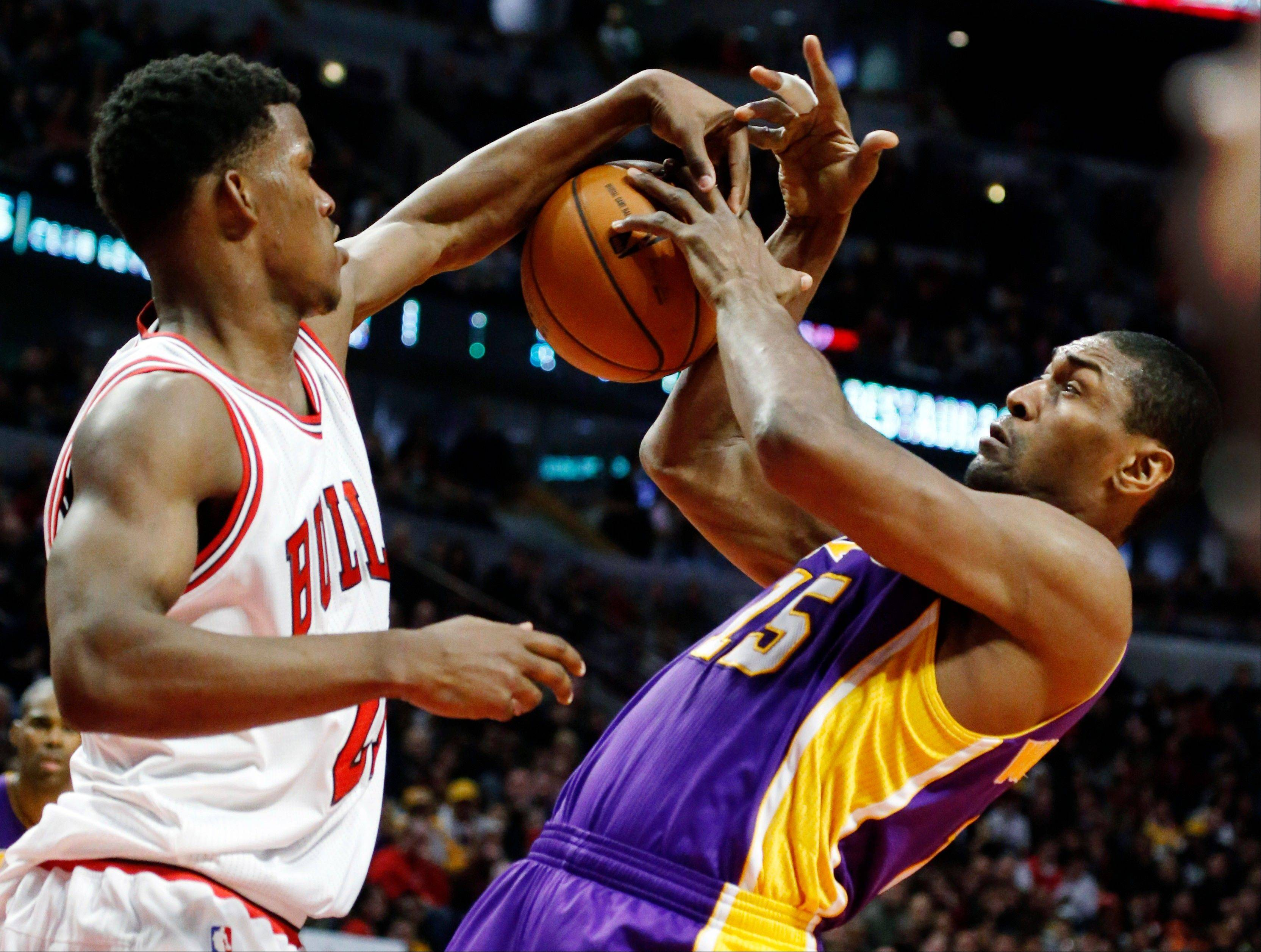 Bulls forward Jimmy Butler (21) knocks the ball from the hands of Los Angeles Lakers forward Metta World Peace during the first half of an NBA basketball game, Monday, Jan. 21, 2013, in Chicago.