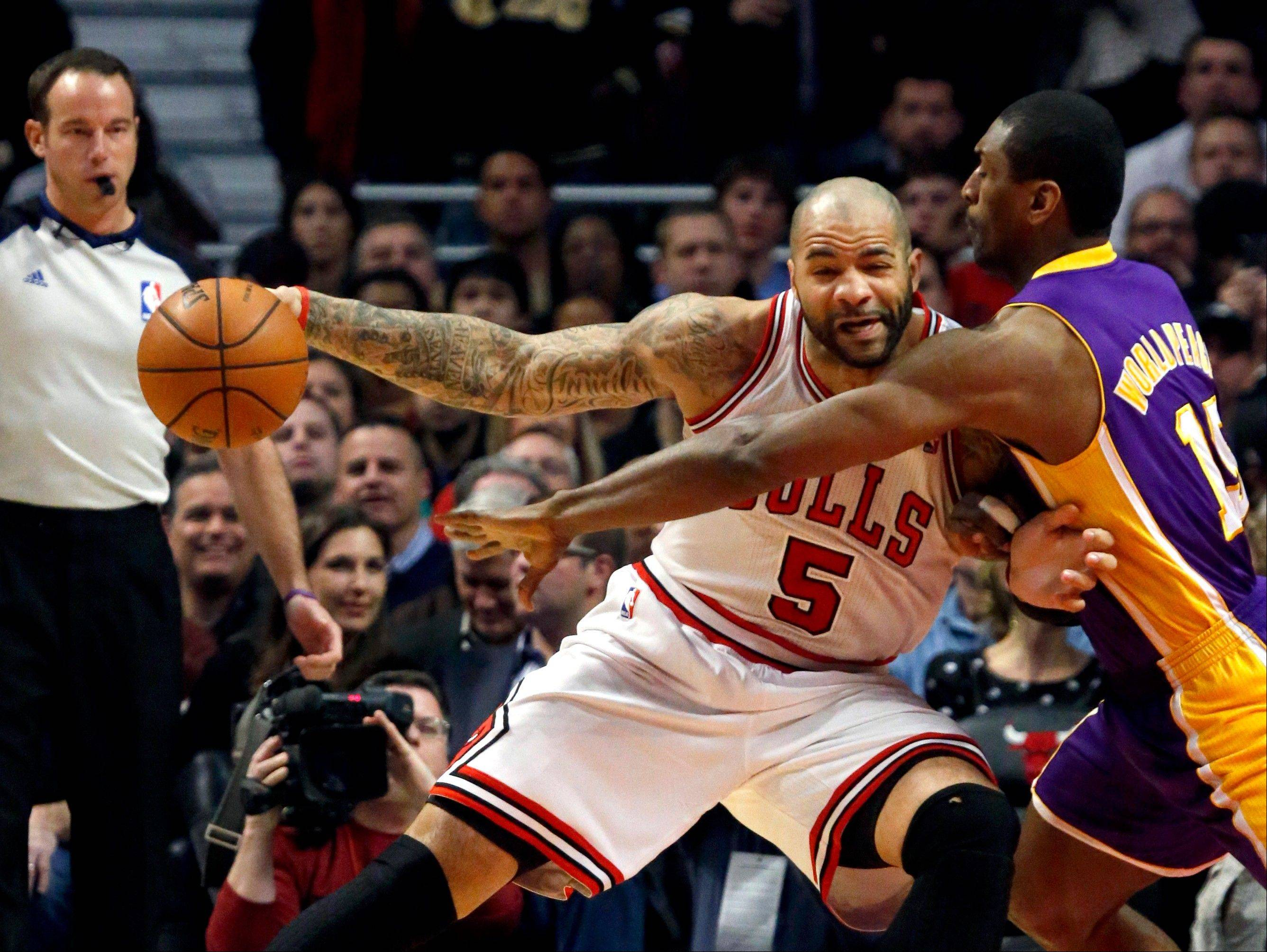 Los Angeles Lakers forward Metta World Peace (15) challenges Chicago Bulls forward Carlos Boozer (5) during the first half of an NBA basketball game, Monday, Jan. 21, 2013, in Chicago.
