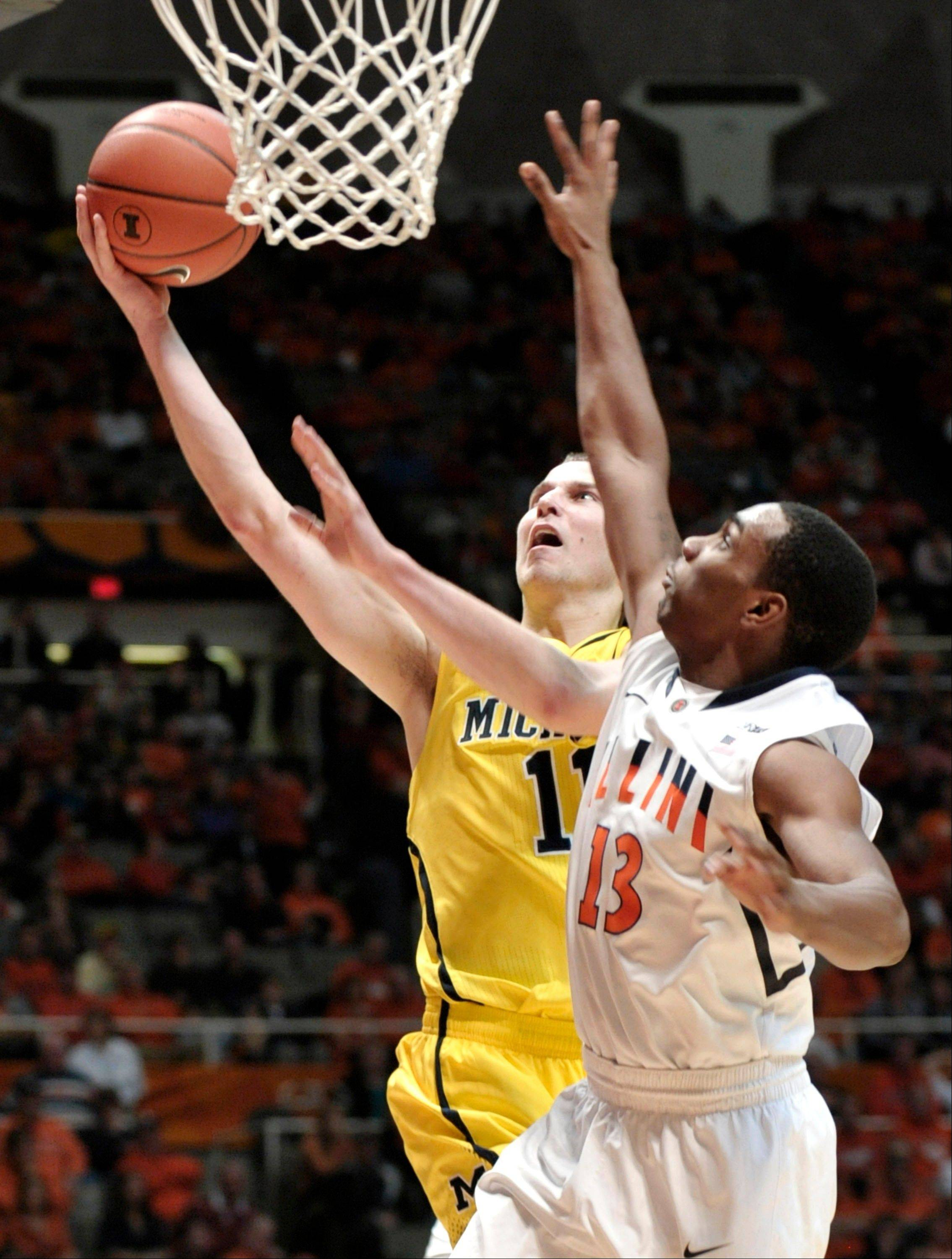 Michigan's Nik Stauskas (11) drives to the basket against Illinois' Tracy Abrams (13) during the second half of their NCAA college basketball game, Sunday, Jan. 27, 2013, in Champaign, Ill. Michigan won 74-60.