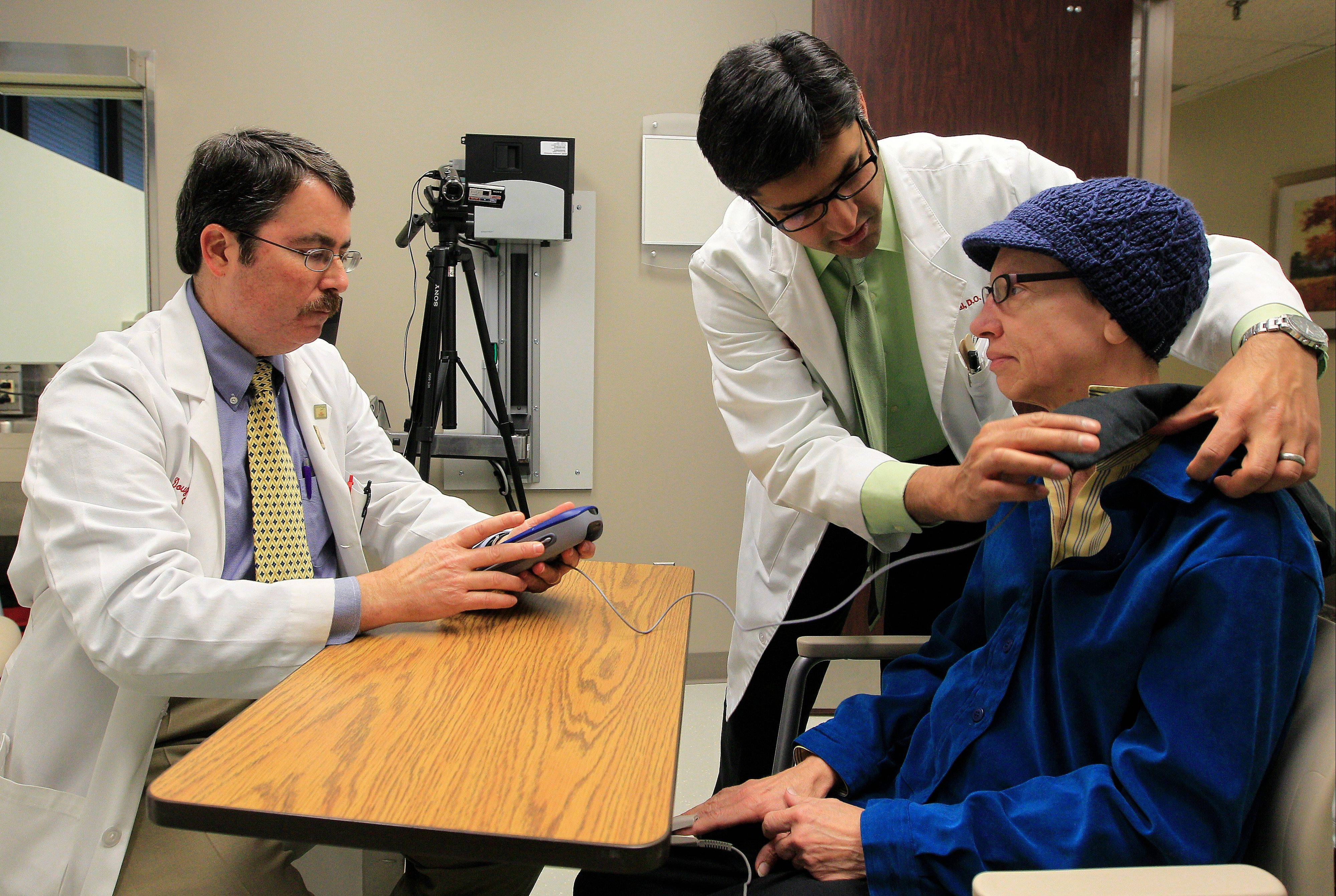 Dr. Doug Scharre, left, and Dr. Punit Agrawal, center, prepare Kathleen Sanford's deep brain stimulation device for monitoring.
