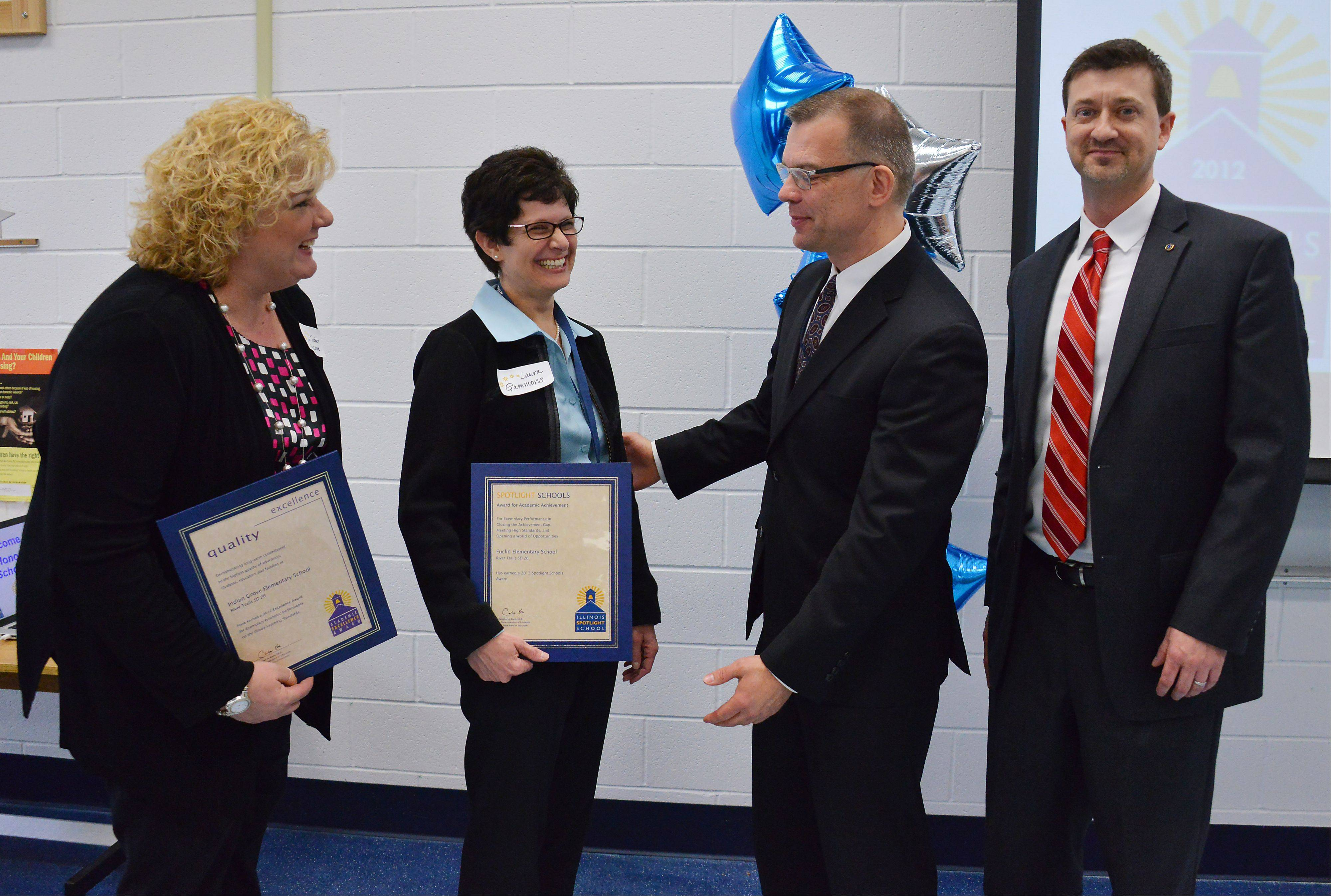 Illinois State Superintendent of Education Christopher Koch awards the Academic Excellence Award on Monday to River Trails Elementary District 26 schools Euclid Elementary School, represented by Lynn Fisher, and Indian Grove Elementary School, represented by Laura Gammons and Dane Delli. The awards were passed out at the John Jay Elementary School in Mount Prospect.