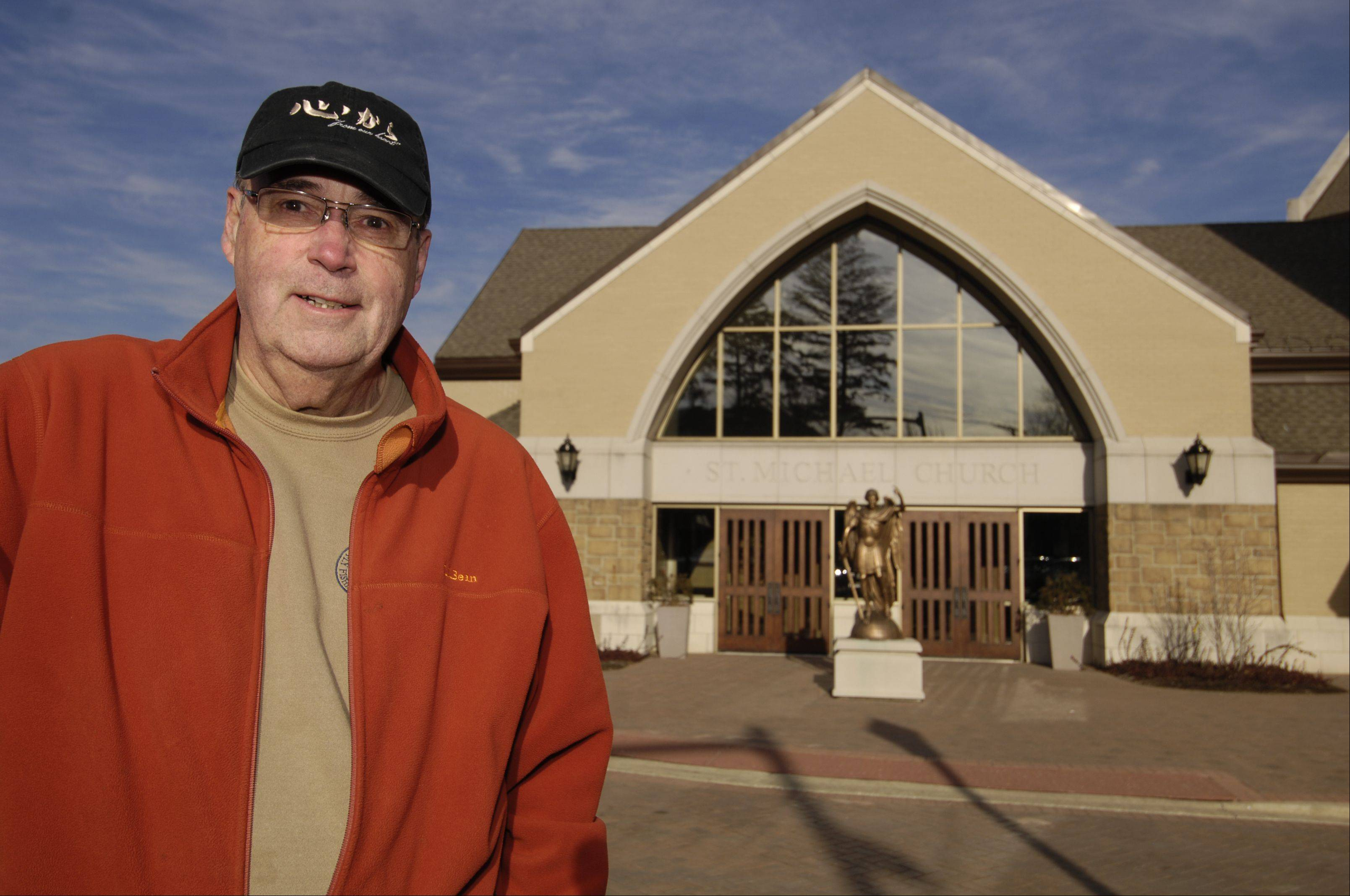 George Carr, a trustee with the Serra Club of DuPage County, stands in front of St. Michael Catholic Church in Wheaton, where he is a member and helps promote the club's mission to encourage people to consider religious vocations.