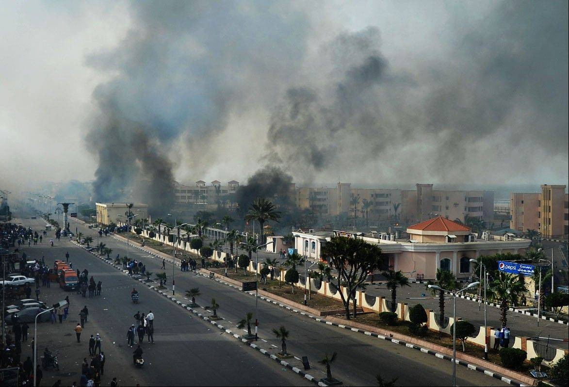 Smoke rises after Egyptian protesters clash with police, unseen, in Port Said, Egypt, Sunday. Violence erupted briefly when some in the crowd fired guns and police responded with volleys of tear gas, witnesses said. State television reported 110 were injured.