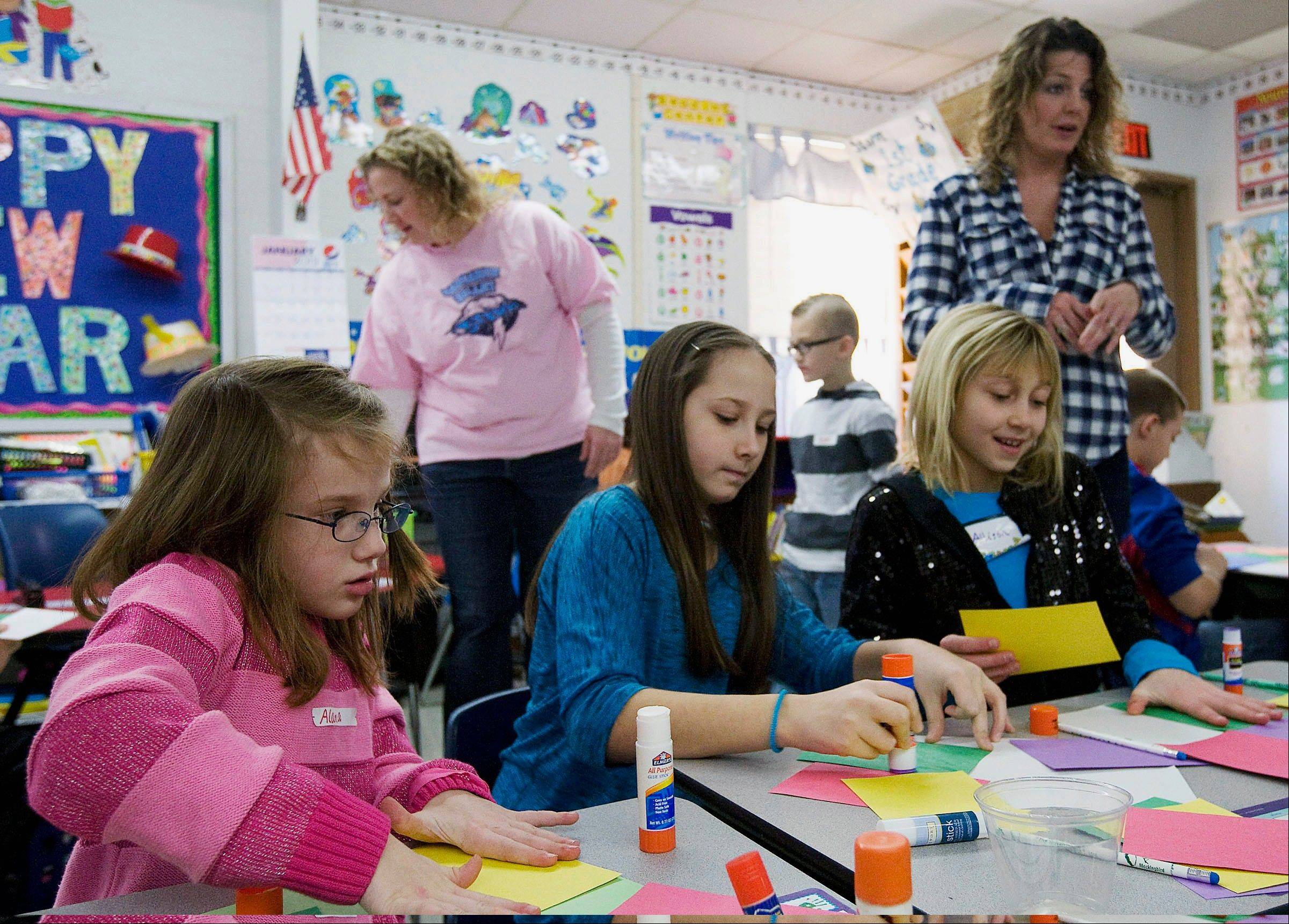 From left, first-grader Alana Schmidt, along with fifth-graders Lexi Lowe and Allison Campbell work with first-grade teacher Teri Runions, far right, to create blocks of pop art during Team Days at Illiopolis Elementary School in Illiopolis.