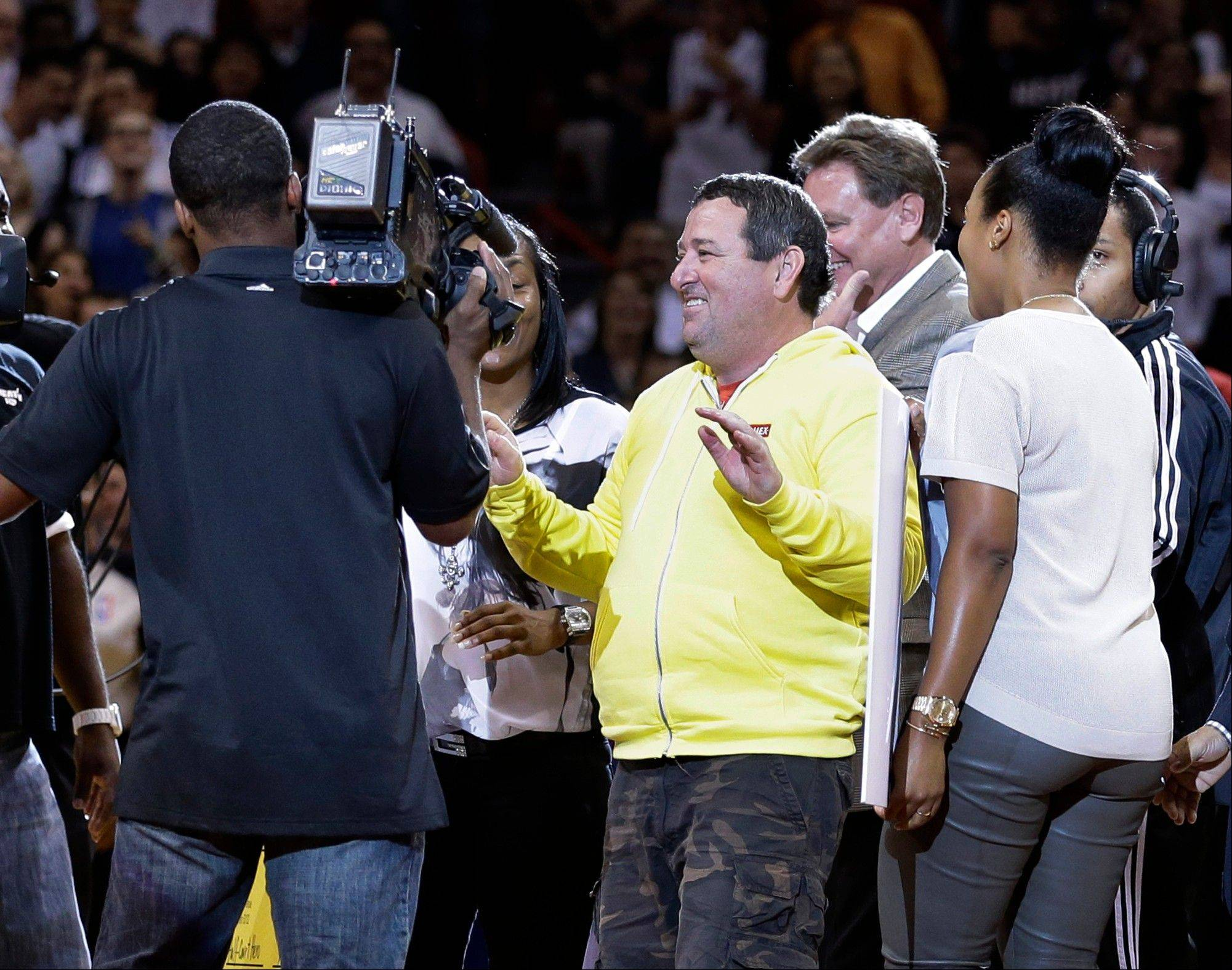 Michael Drysch, center, a 50-year-old computer technician from McHenry celebrates after making a half-court shot to win $75,000 and a hug from LeBron James, during the second half between the Miami Heat and the Detroit Pistons, Friday in Miami. As part of a contest sponsored by James' foundation, Drysch hit a one-handed hook shot from midcourt between periods in the game.
