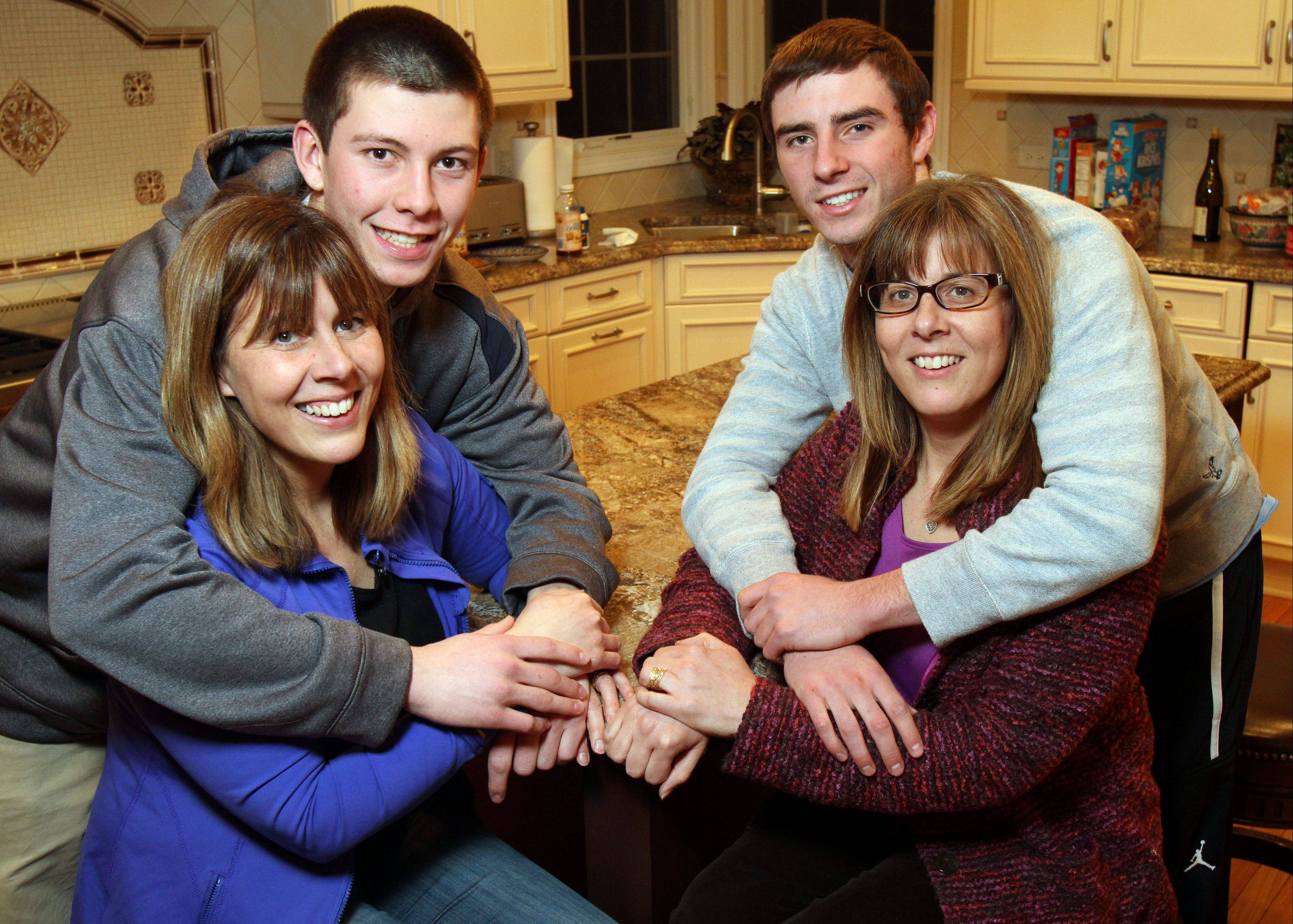 Ryan Roach and his mother Kim, left, and John Repplinger and his mother Justine. The boys are cousins and both guards on Lake Zurich�s boys basketball team; the moms are twins.