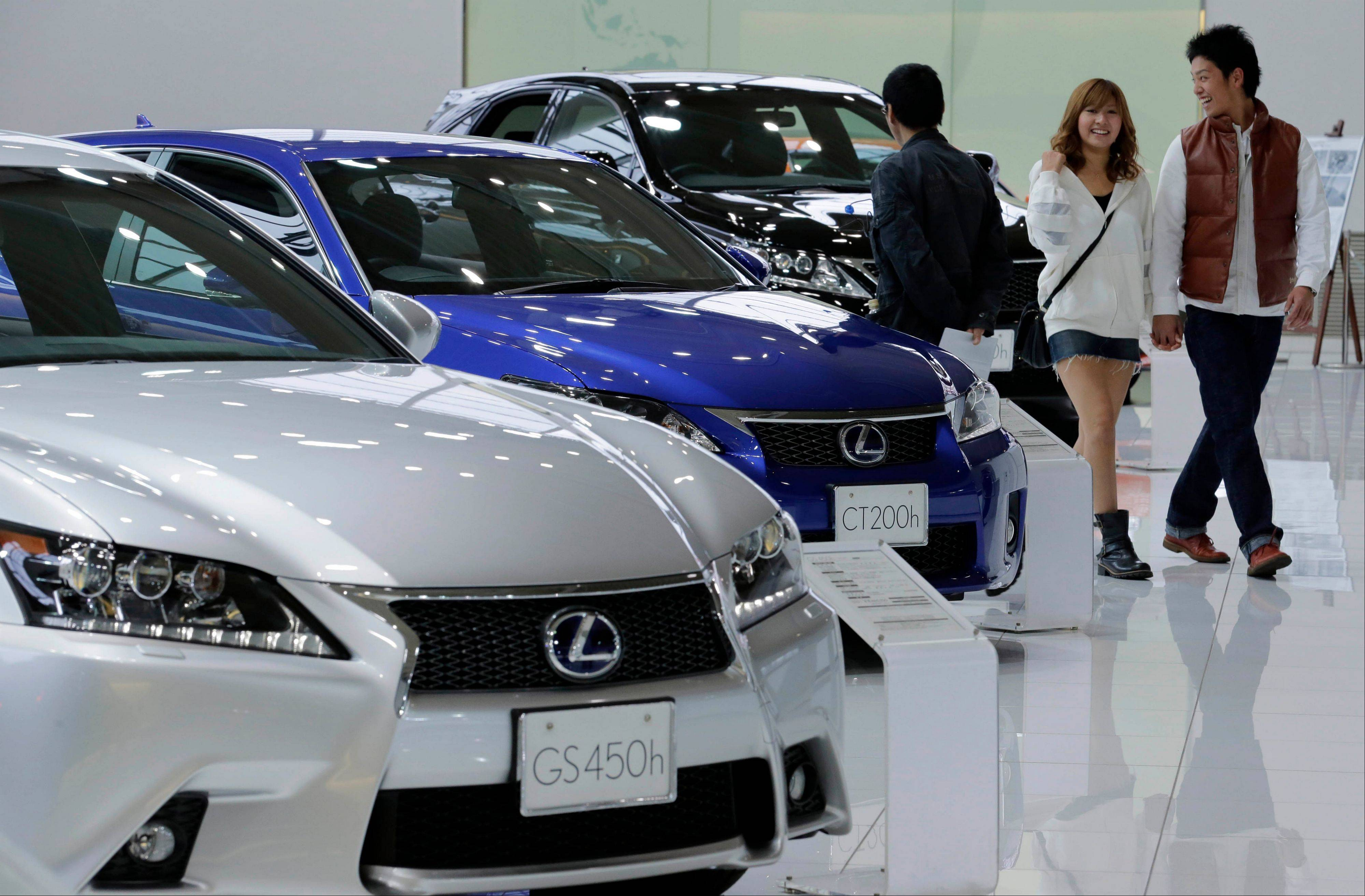 A couple walk by Lexus models displayed at a Toyota Motor Corp. showroom in Tokyo. Now it's official: Toyota is once again the world's top automaker.