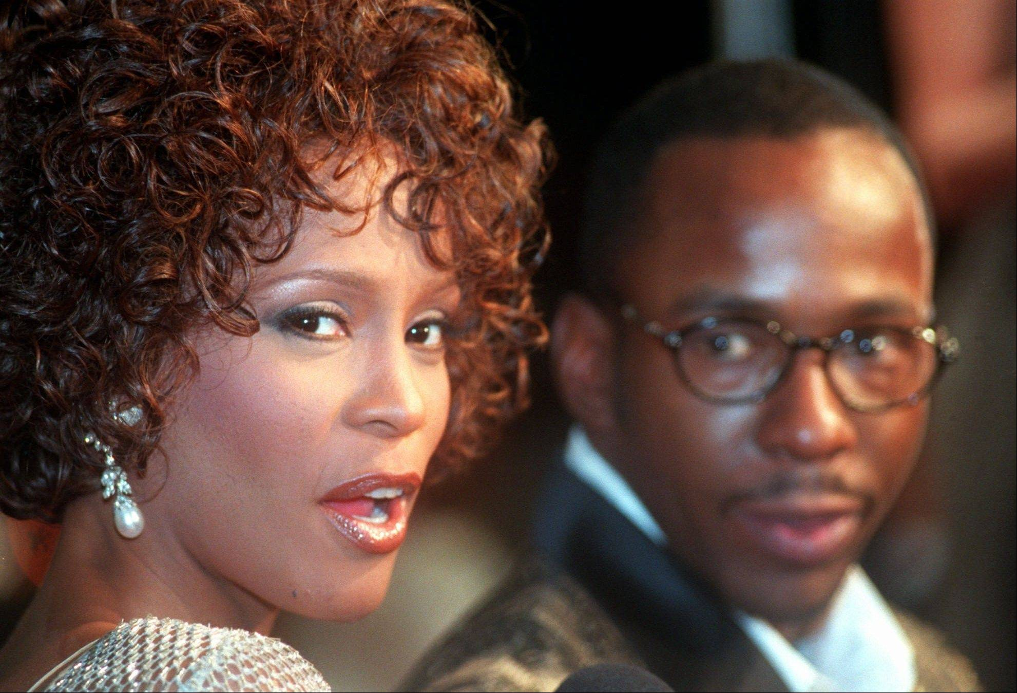 "In this Oct. 13, 1997 file photo, Whitney Houston looks over her shoulder as her husband Bobby Brown looks to her at a film premiere in Los Angeles. Houston's mother, Cissy, says she believes her daughter wouldn't have had to fight so hard to stay sober if it weren't for Brown. ""To me, he never seemed to be a help to her in the way she needed,"" Cissy Houston writes."