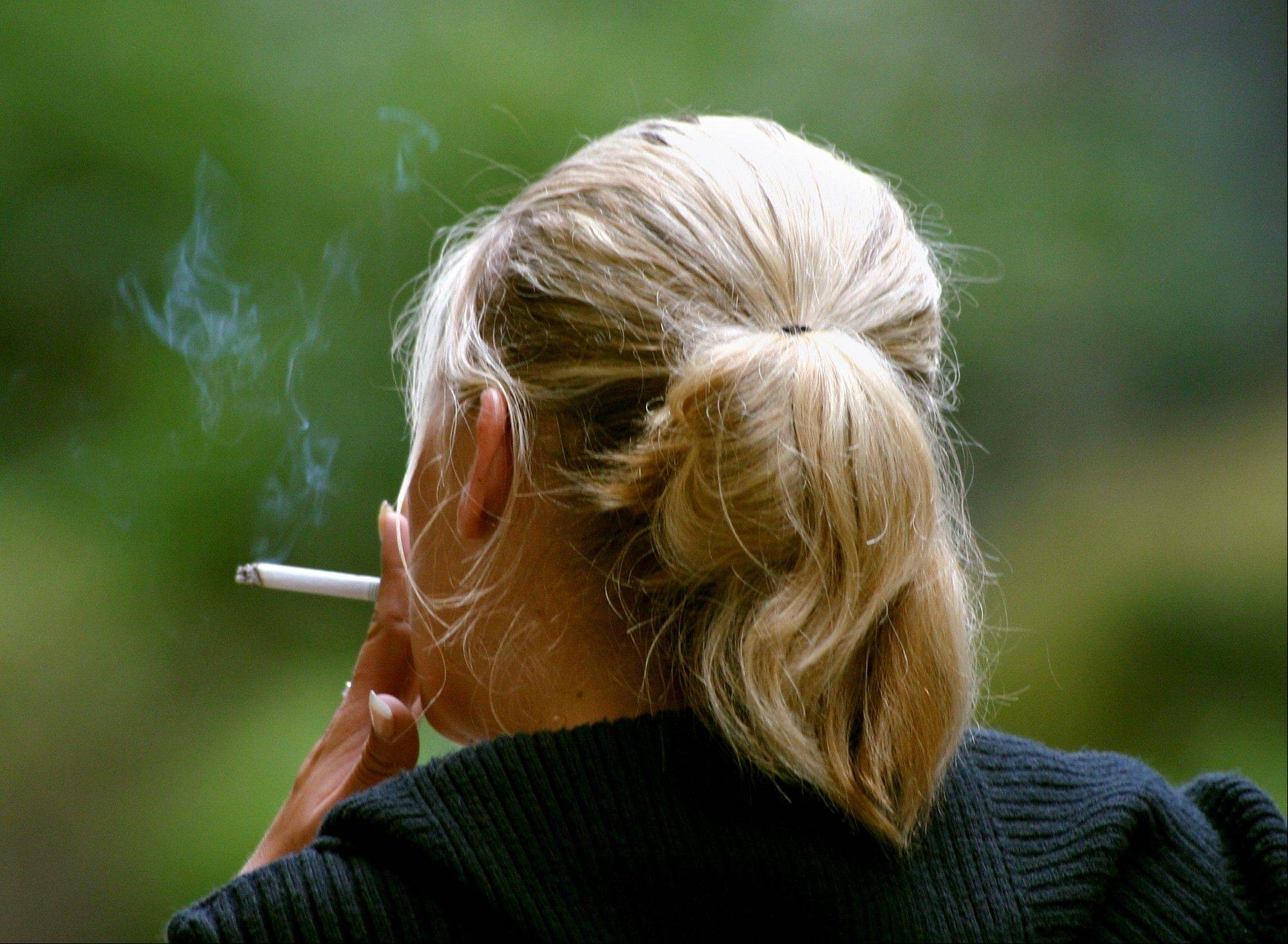 A woman smokes a cigarette during a break from work in downtown Chicago. New research published in the New England Journal of Medicine finds that women who smoke today have a much greater risk of dying from lung cancer than they did decades ago compared to those who never smoked.