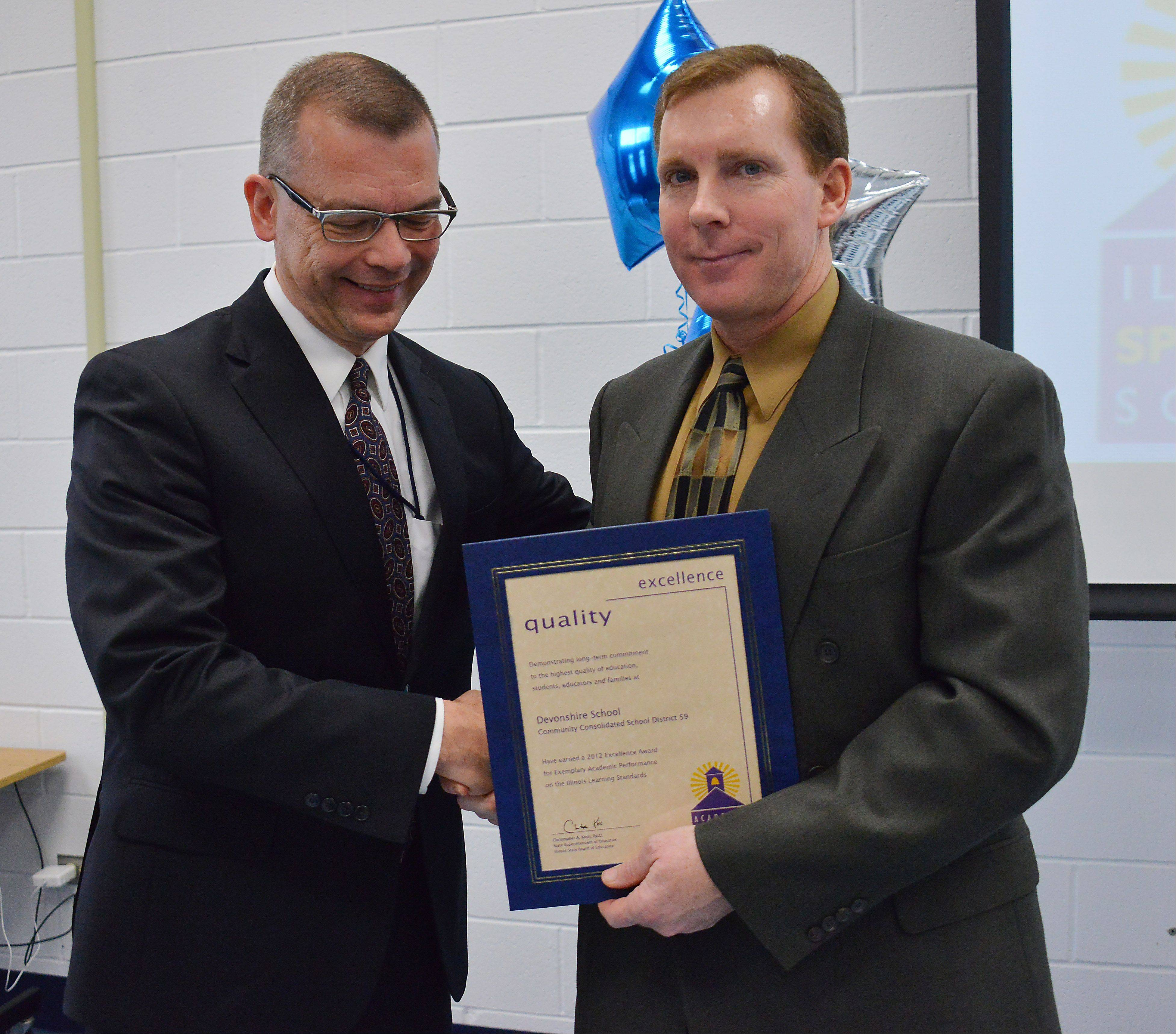 Elk Grove Township District 59's Devonshire Elementary School Principal Randy Steinkamp (right) received the Academic Excellence Award on Monday from State Superintendent of Education Christopher Koch.