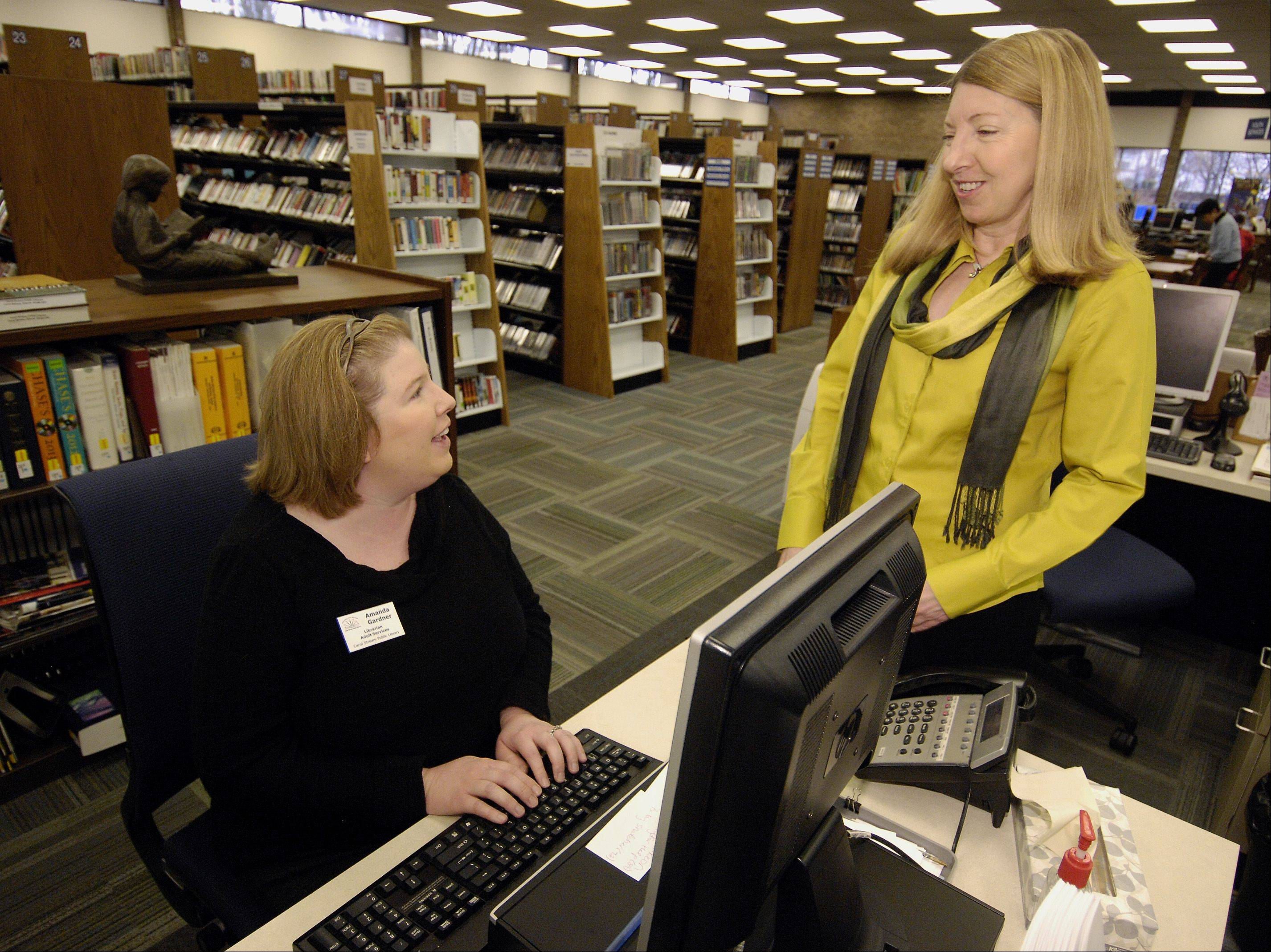 Carol Stream Public Library employee Amanda Gardner talks with new library Director Susan Westgate on Westgate's first day Monday.
