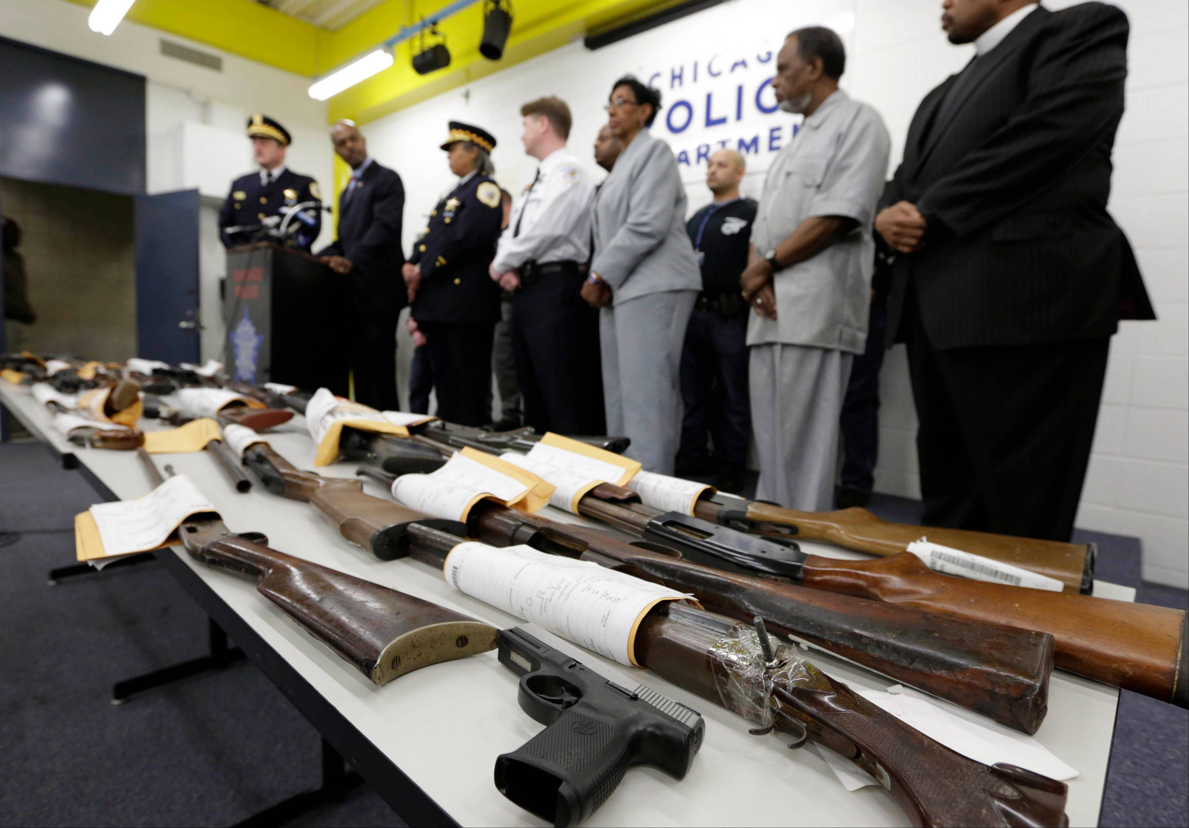Chicago police, elected officials, clergy, and community members show some of the recovered firearms from the 574 seized to date beginning Jan. 1. Police say the homicide rate is a reflection of the city's gang problem and a proliferation of guns.