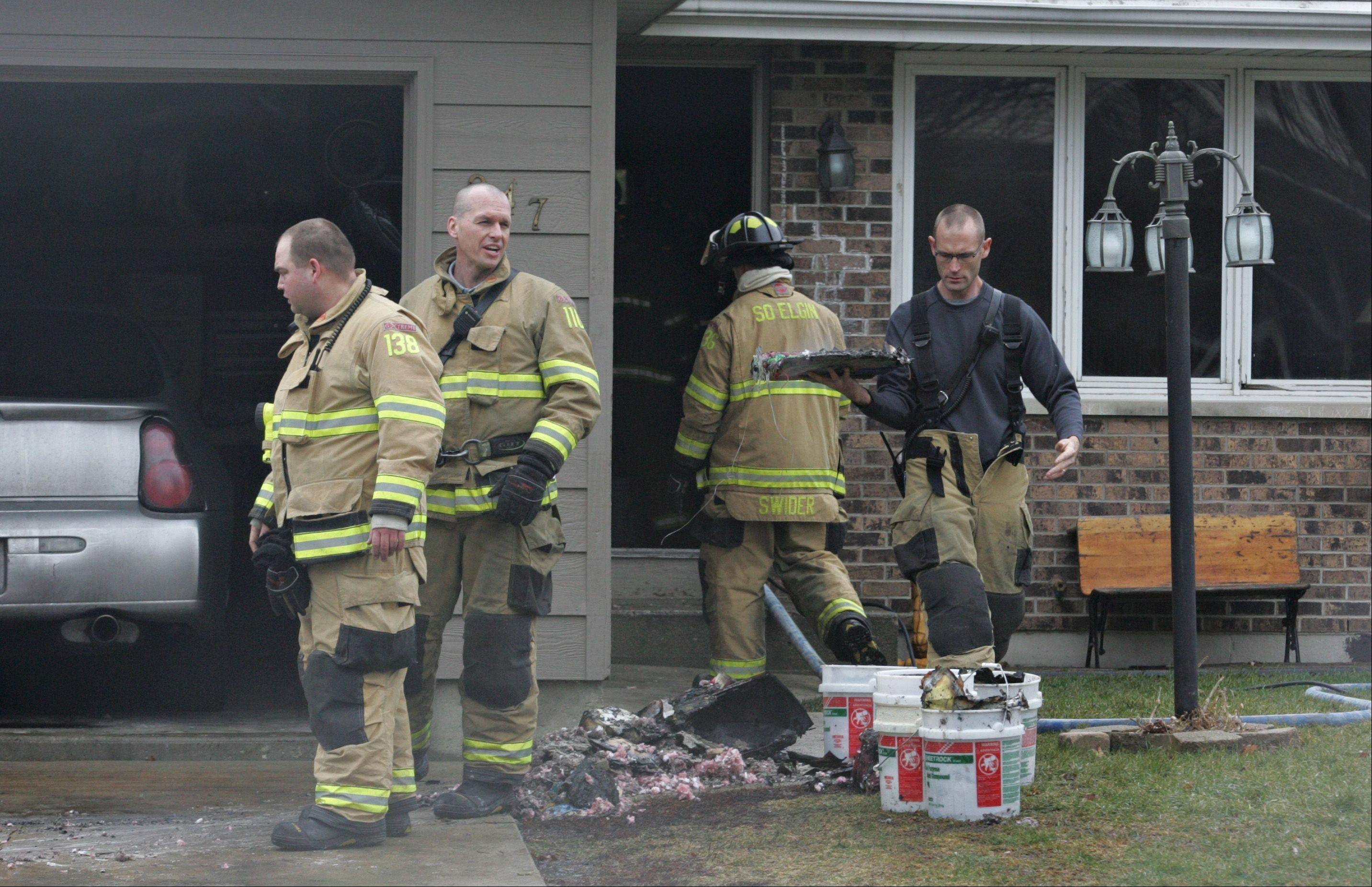 South Elgin firefighters remove some of the burned contents Monday from a home on the 900 block of Kane Street in South Elgin.