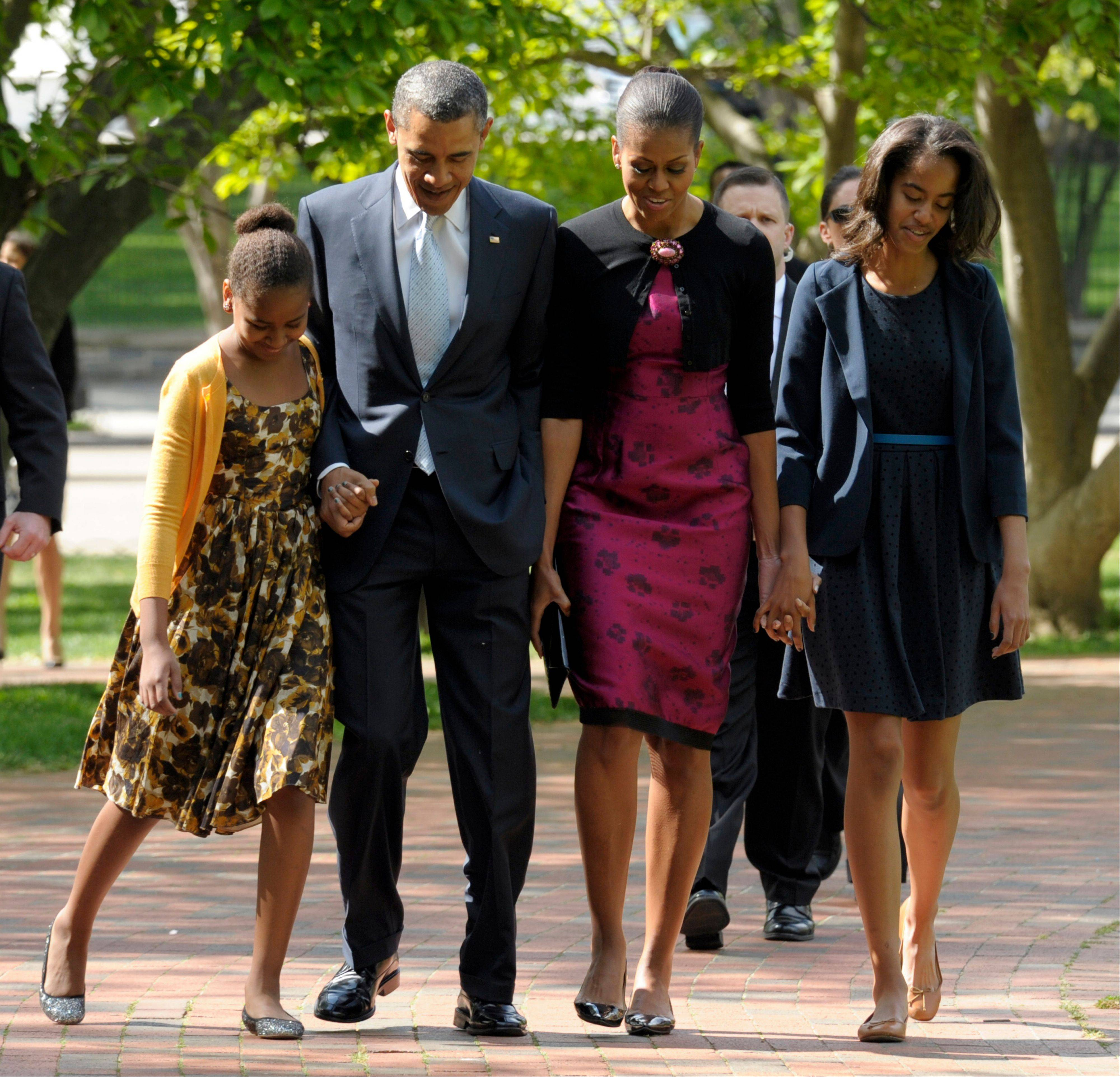 President Barack Obama, first lady Michelle Obama, daughters Malia, right, and Sasha walk across the square from the White House to St. John's Episcopal Church for Easter service in Washington.