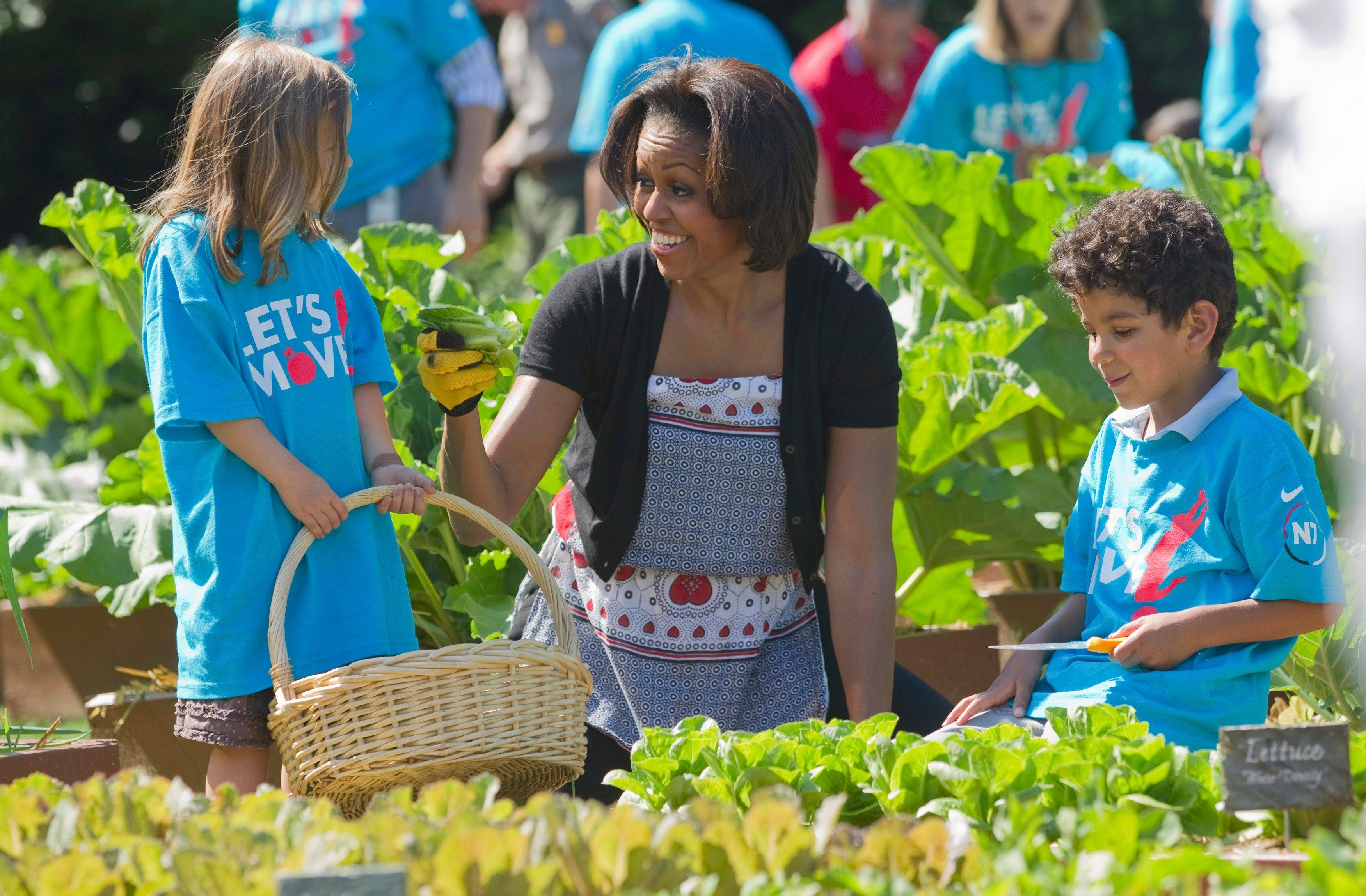 "Michelle Obama tends the White House garden in Washington, with a group of children as part of the ""Let's Move!"" campaign."