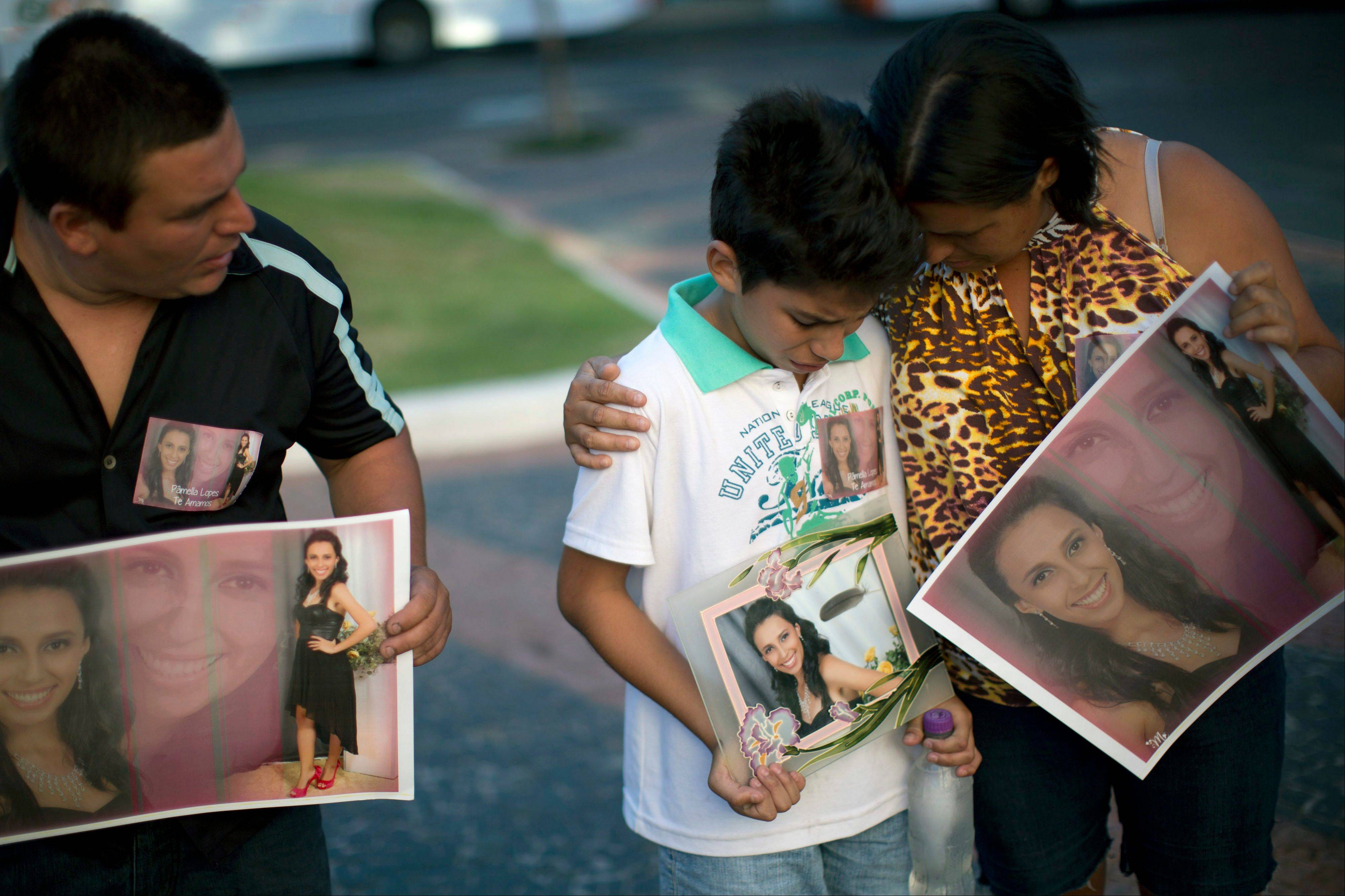 Relatives hold photographs of Pamella Lopes, who died in a nightclub fire, as they stand a public square near the nightclub in Santa Maria, Brazil, Monday.