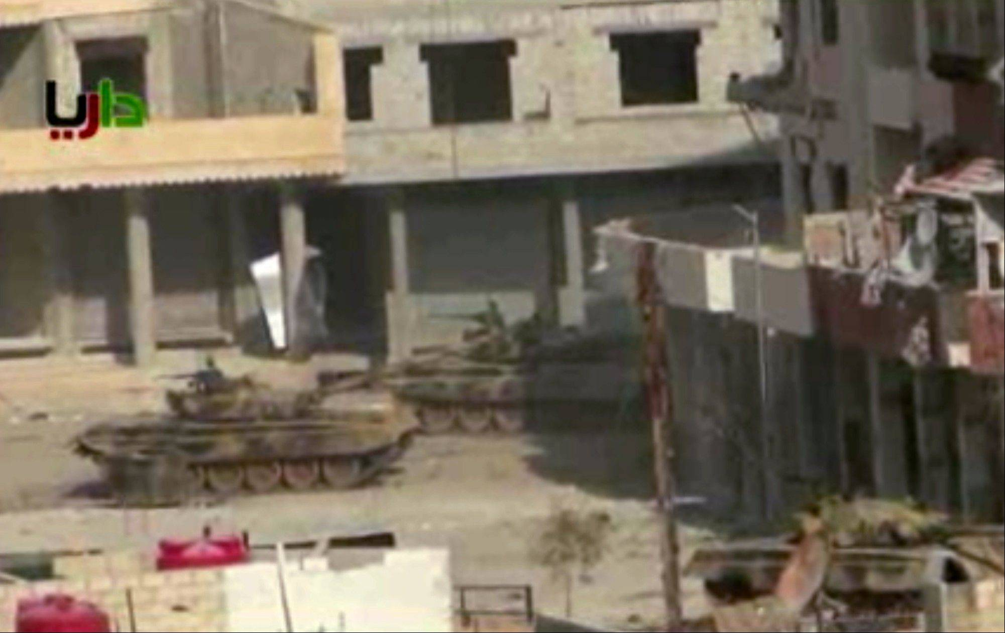 In this from video obtained from the Sham News Network, which has been authenticated based on its contents and other AP reporting, a pair of what activists say are tanks from President Bashar Assad regime in sit in a street in the Daraya neighborhood of Damascus, Syria, just before one of them fires a shot Friday. Troops battled rebels around Damascus in an effort to dislodge opposition fighters who have set up enclaves around the capital, including Daraya and Zabadani.