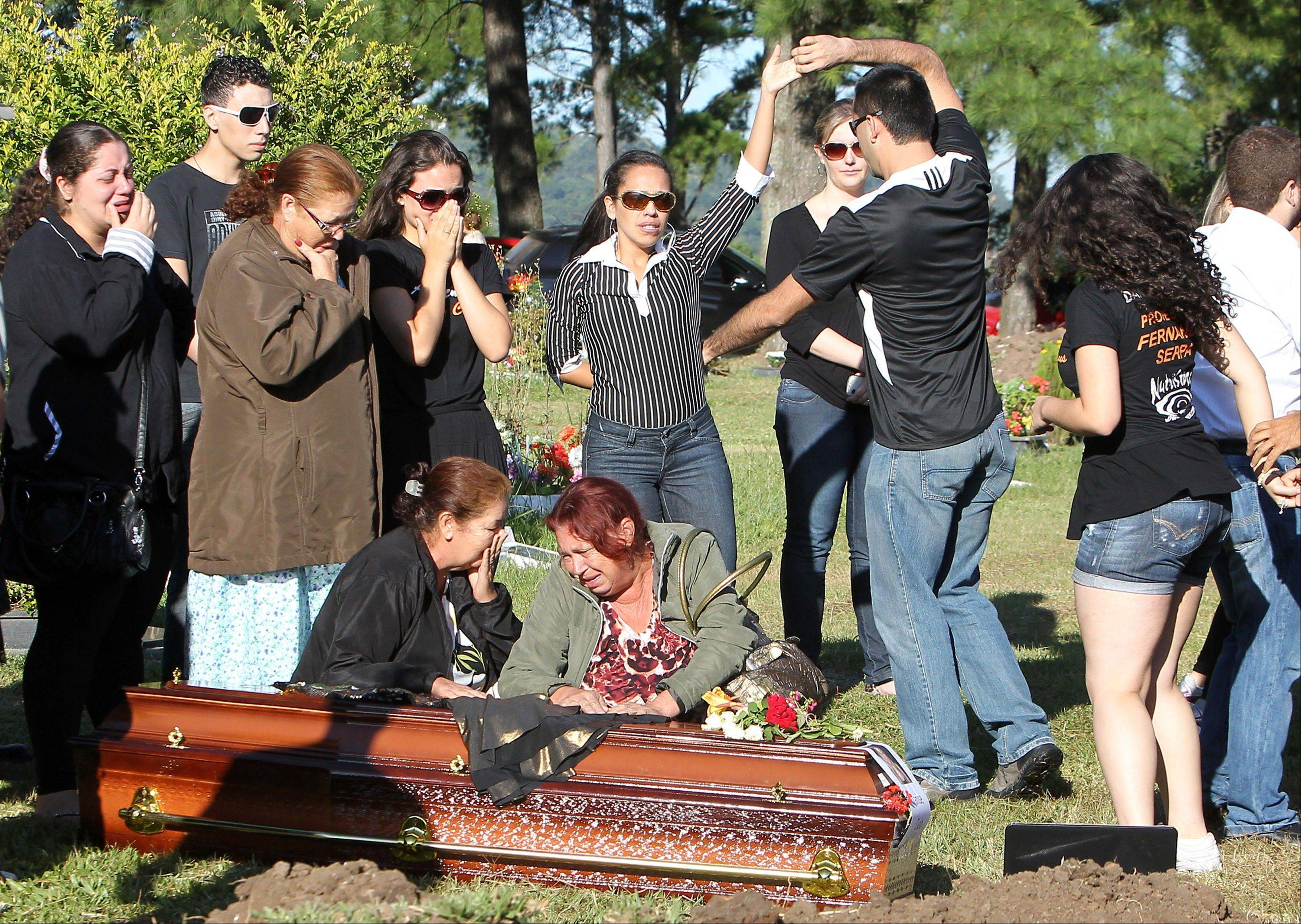 Relatives and friends dance and mourn next to the coffin during the burial of fire victim Tanise Cielo at a cemetery in Santa Maria city, Rio Grande do Sul state, Brazil, Monday. The city in southern Brazil started burying the 233 people killed in Sunday's fire at the Kiss nightclub after the conflagration caused by a band's pyrotechnic display.