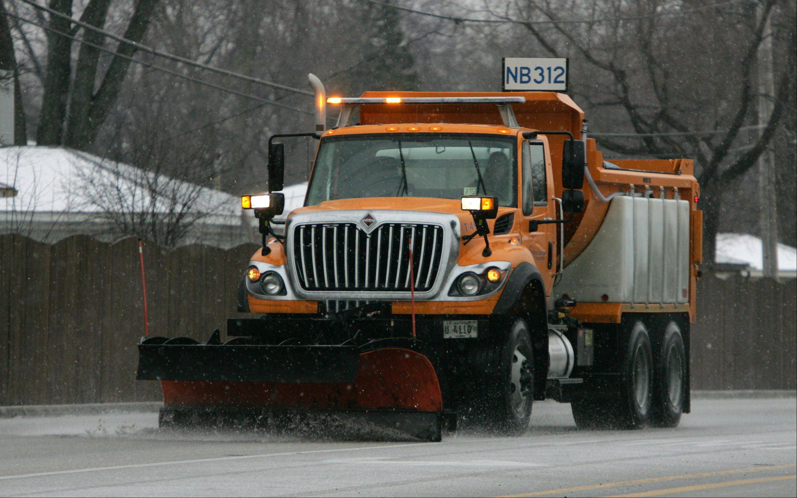 An Illinois Department of Transportation truck salts the roads along Elmhurst Road in Wheeling yesterday as an ice storm hit the area causing difficult driving conditions.