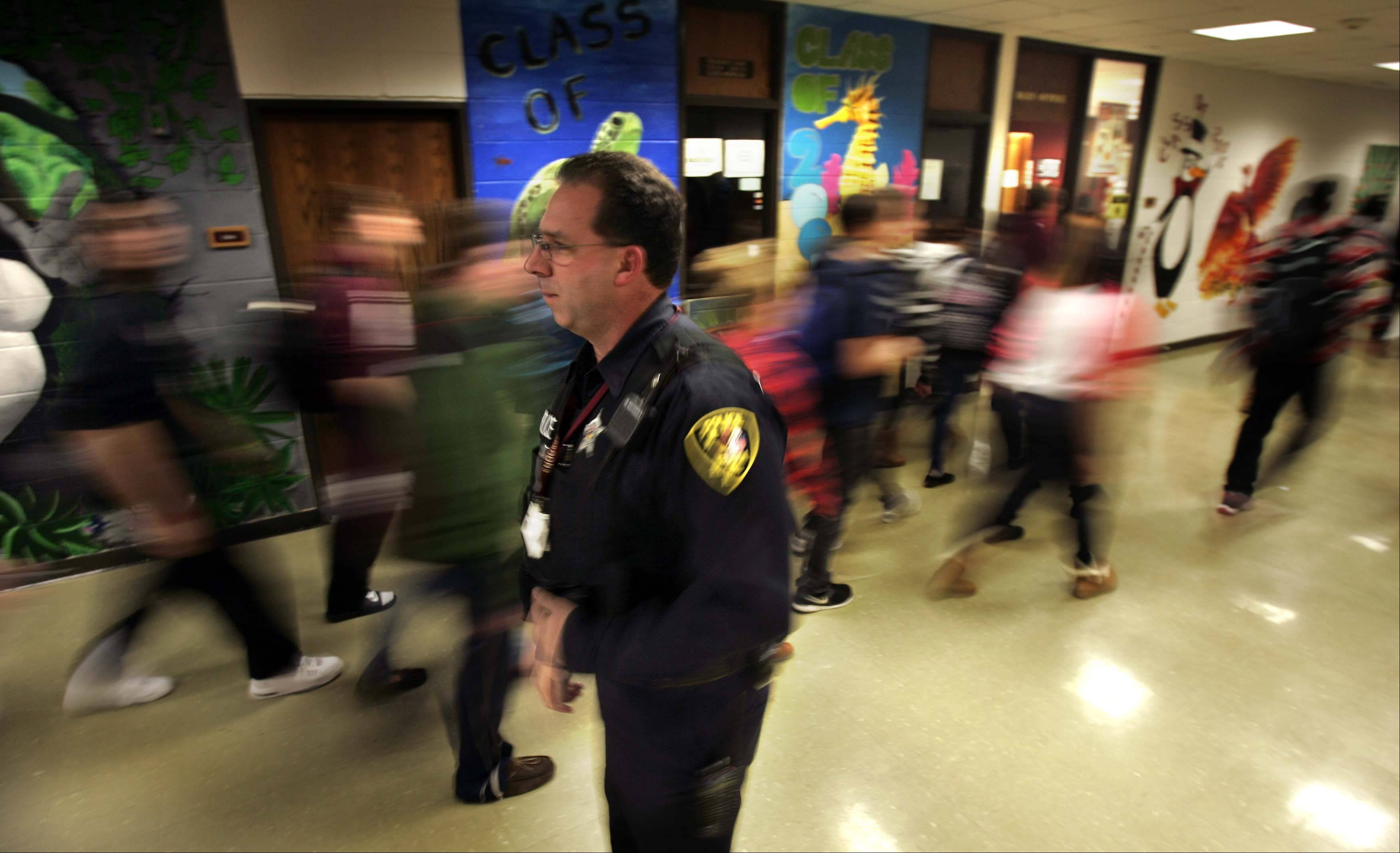 Elgin police Det. Bill Wood greets many of the more than 2,500 Elgin High School students by name as they head to class during a passing period Thursday. He supports specialized training for officers stationed in schools.
