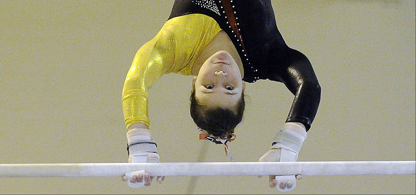 Caiti Poland of Schaumburg performs her routine on the uneven parallel bars at the Prospect regional on Monday.