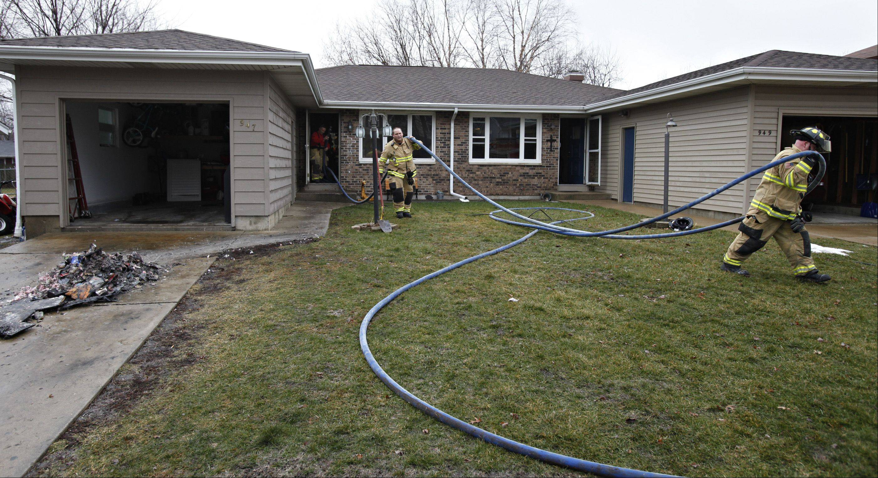 Two South Elgin firefighters bring out a hose line after battling a fire Monday on the 900 block of Kane Street in South Elgin. Firefighters said a dog may have sparked the fire by jumping for a pizza box on a stove, knocking the stove�s burner setting to the �on� position.