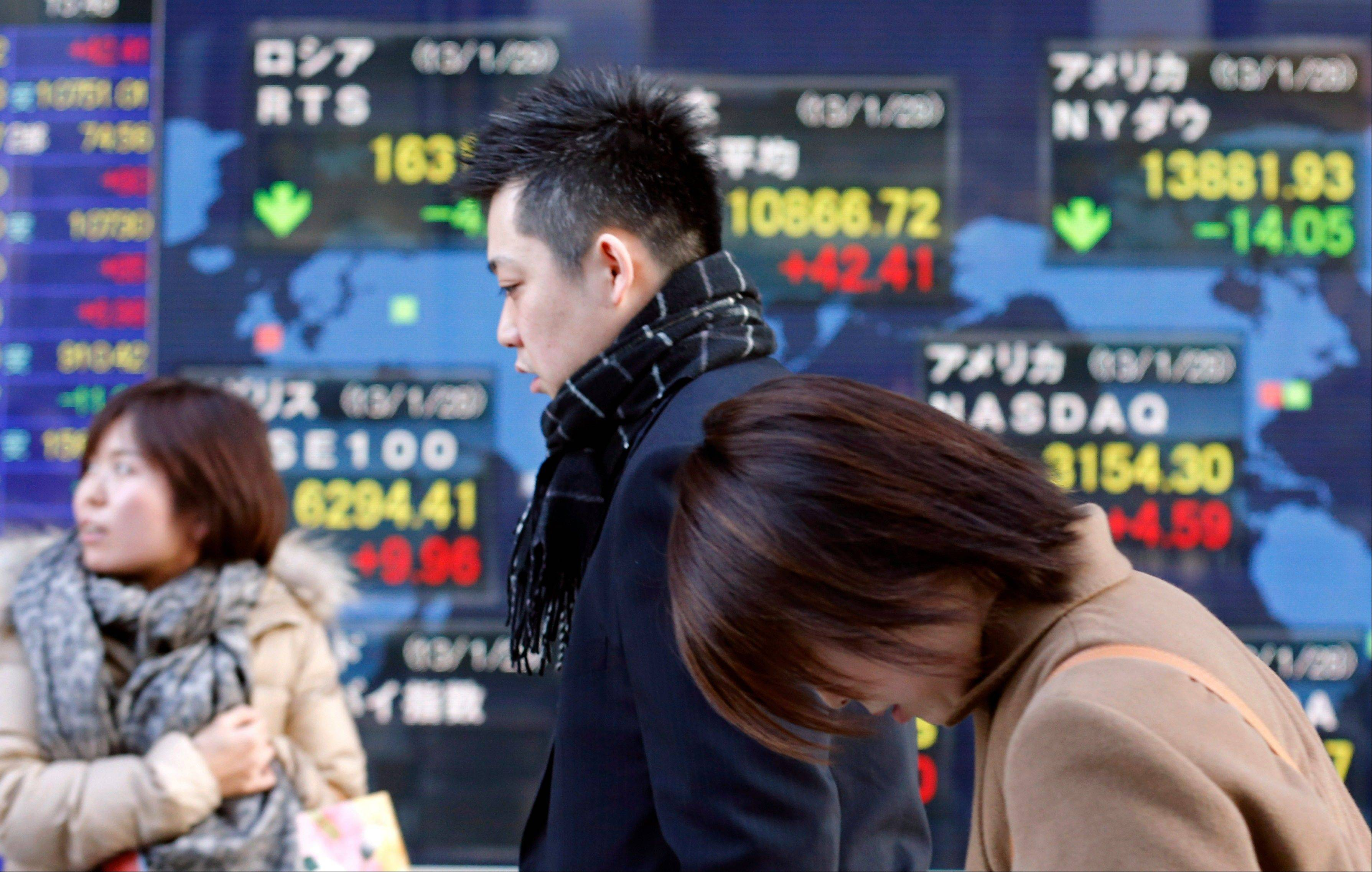 People walk by an electric stock index display of a securities firm in Tokyo Tuesday.
