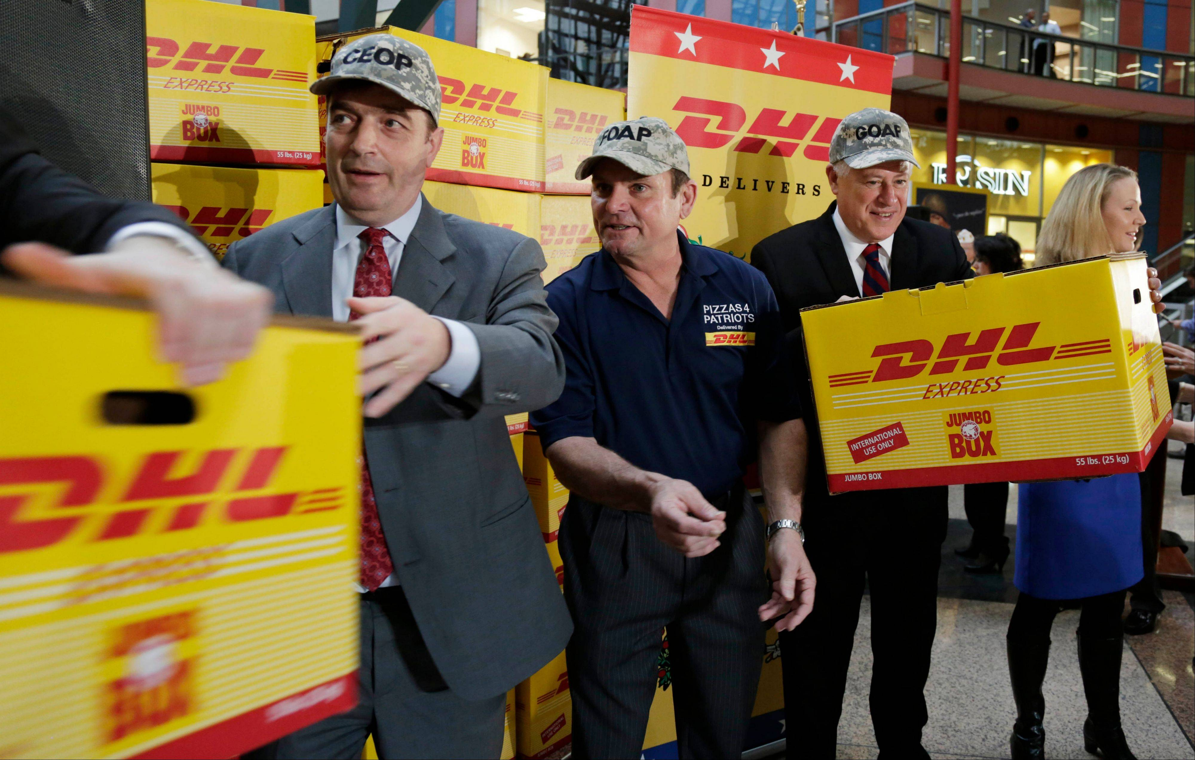 Ian Clough, left, CEO of DHL Express, Elk Grove resident Mark Evans, center, of Pizza 4 Patriots, and Gov. Pat Quinn on Tuesday help load boxes that will hold thousands of Chicago-style pizzas headed overseas to members of the military in time for Super Bowl Sunday.