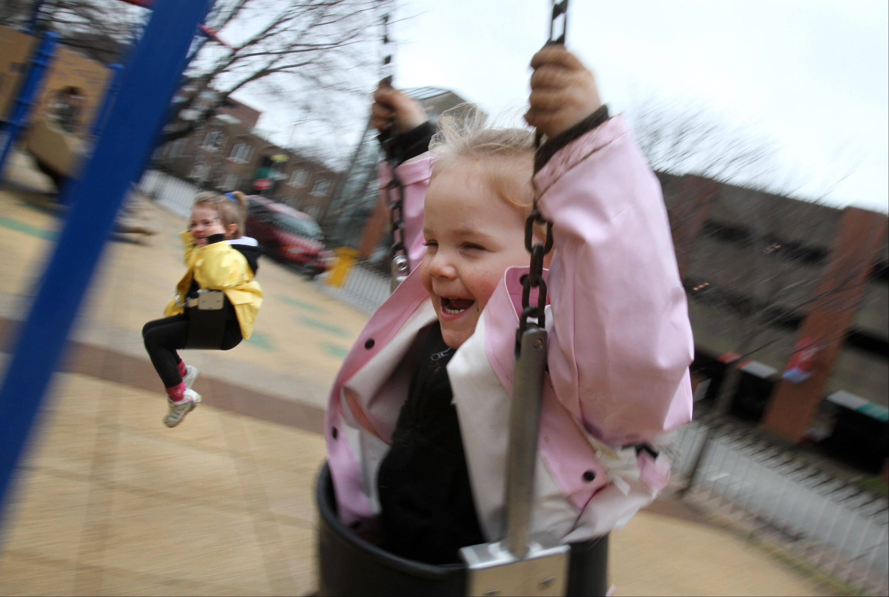 Three-year-old Madalynn Kerley with her sister Melody, 4, and mother Michelle, all of Palatine, enjoy the swing at North School Park in Arlington Heights .