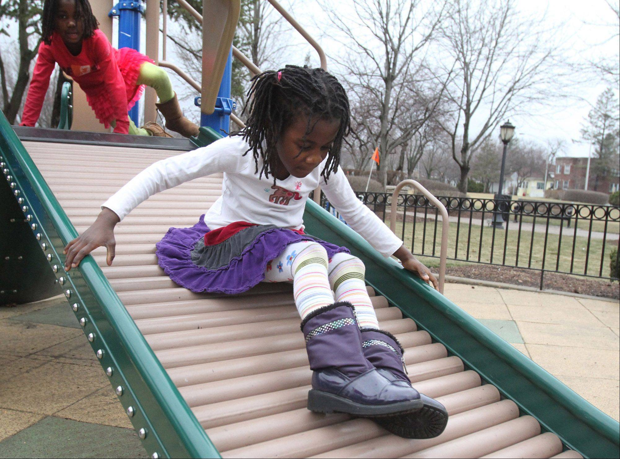 Kea Bucataru, 7, rides down the slide, with her sister Corrie, 5, both of Arlington Heights, trailing behind her at North School Park in Arlington Heights on Tuesday.