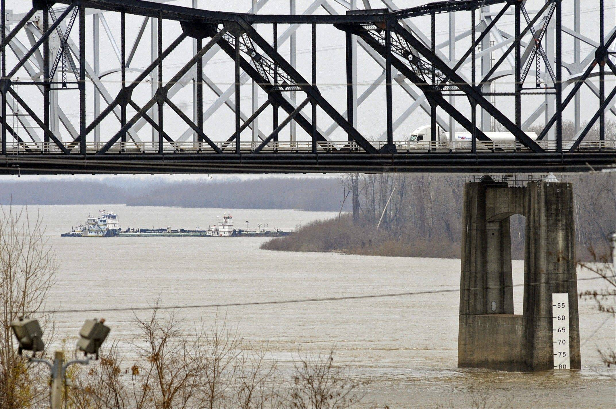 Cleanup crews with booms skimmed oily water from the Mississippi River Monday, a day after a barge with more than 80,000 gallons of oil struck a railroad bridge near Vicksburg, spreading a sheen of light crude that kept part of the waterway shut to ship traffic Monday, authorities said.