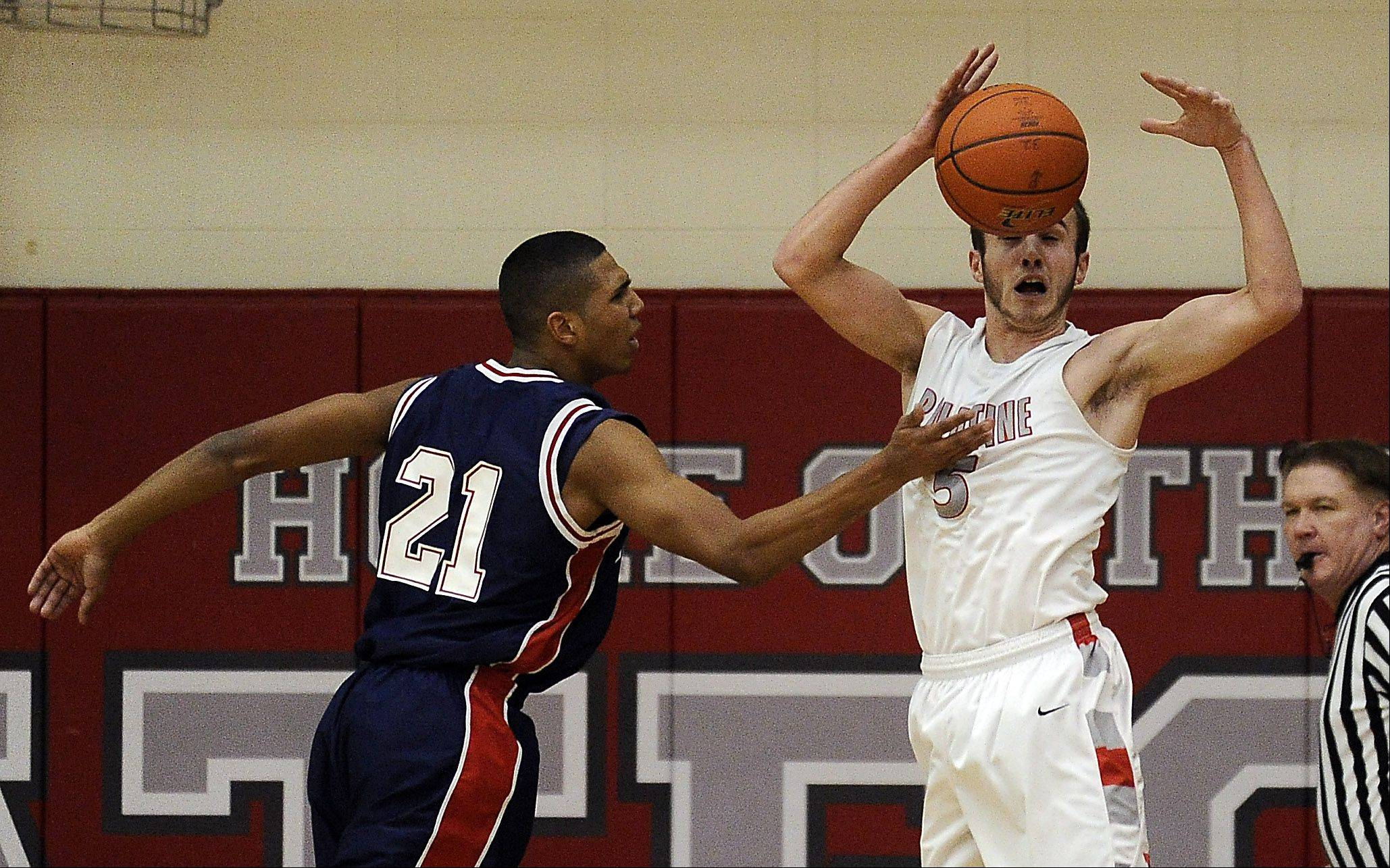 Palatine's Chris Macahon tries to control the ball and keep it away from Conant's D'Angelo McBride in the first half of boys varsity basketball at Palatine High School on Thursday.
