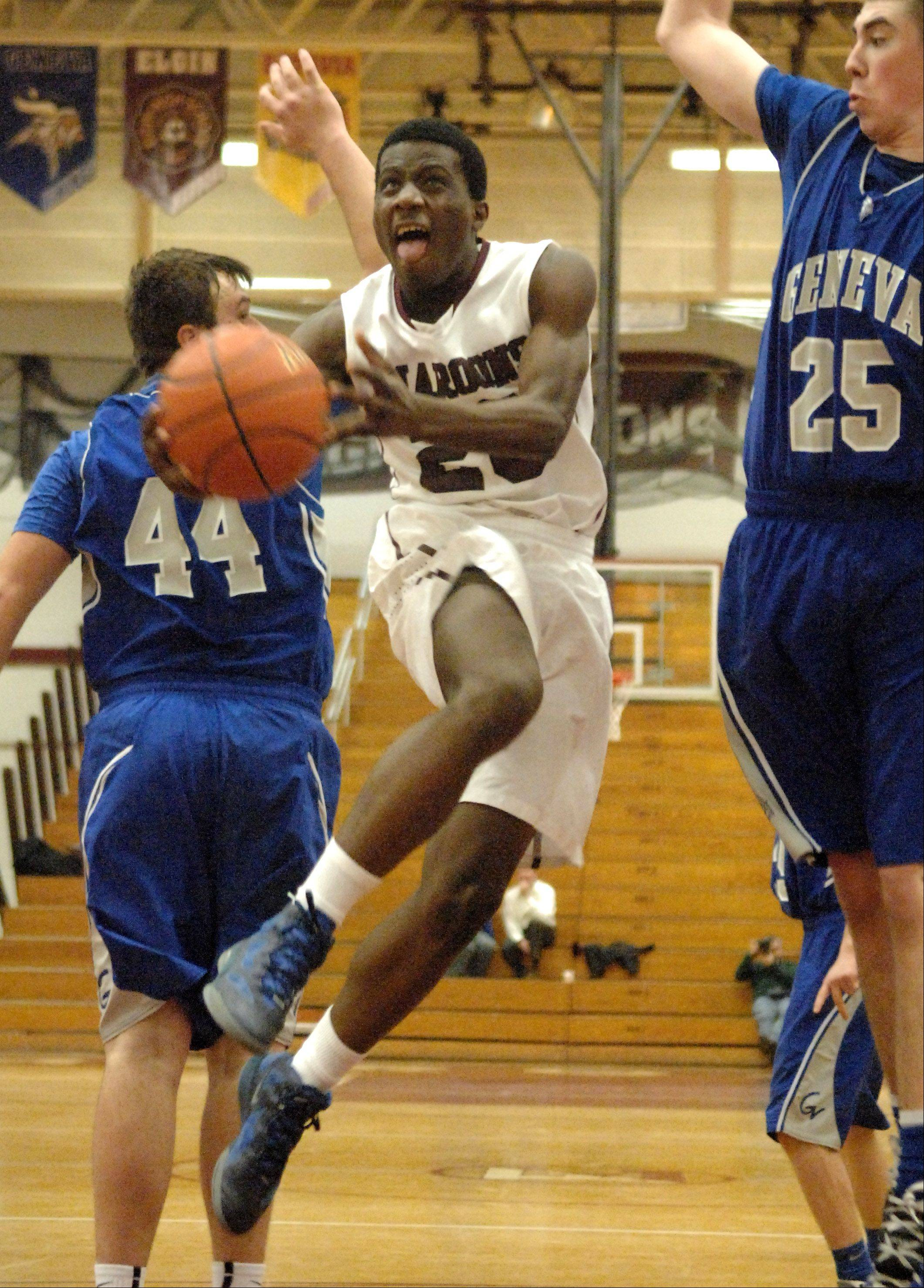 Elgin's Isaiah Butler drives to the basket between two Geneva defenders during Thursday's game in Elgin.