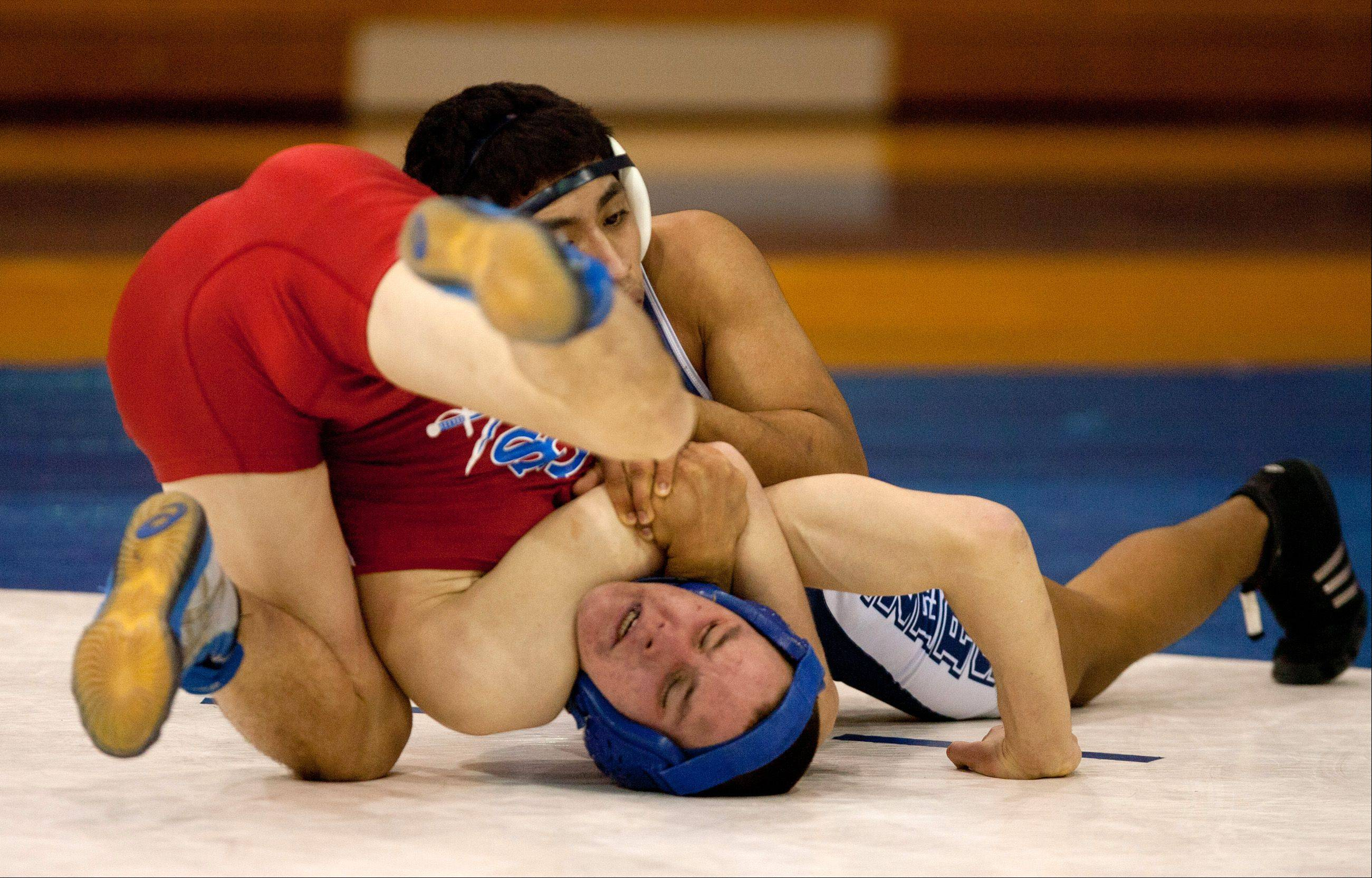 Addison Trail's Aaron De La Cruz, top, beats Glenbard South's Mark Cizek in the 132-pound weight class.