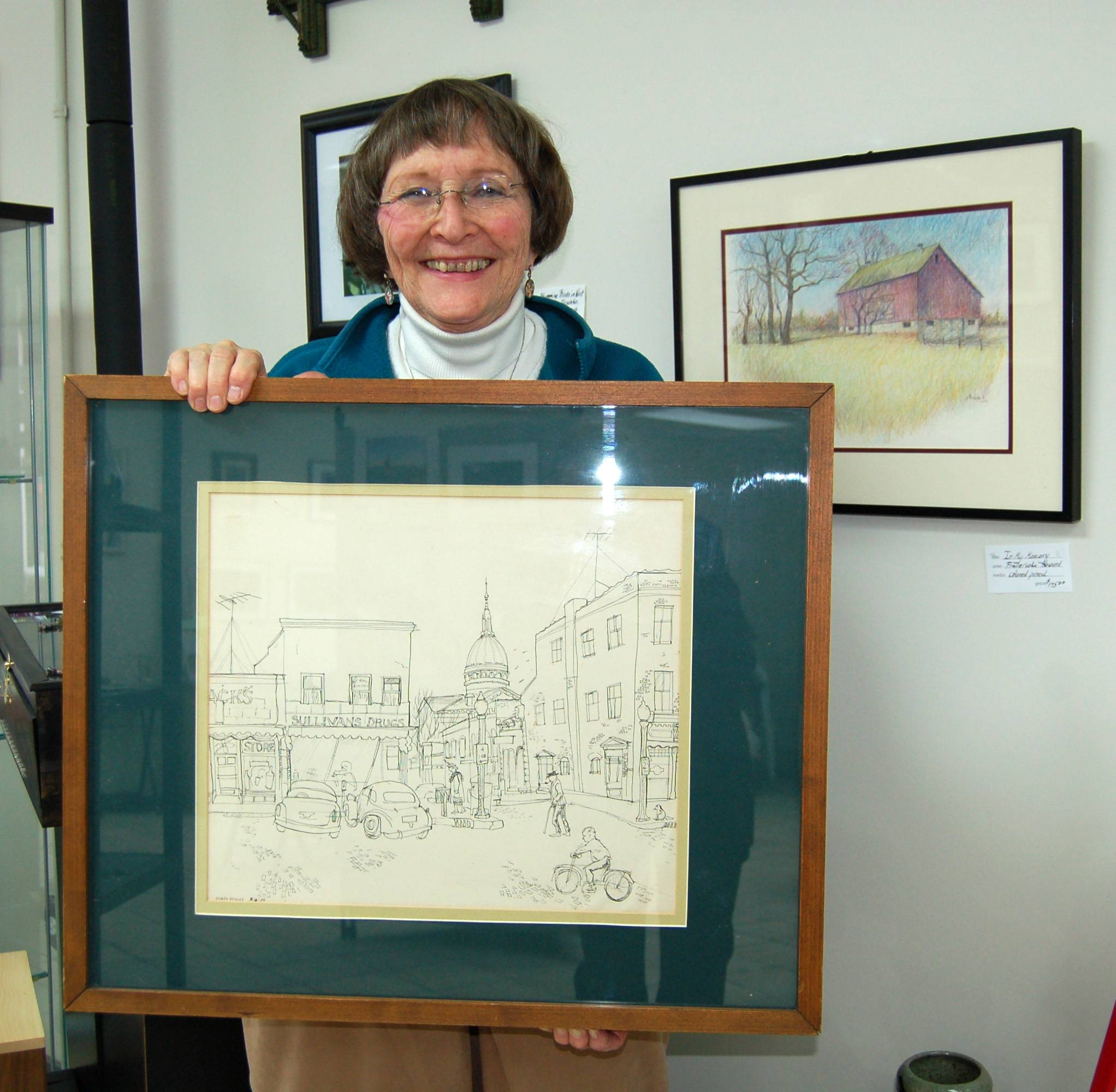 "Fredericka Krauss Howard is holding an ink sketch titled ""Carlinville Square,"" a piece from her original 1953 art portfolio from Blackburn College.  The image will be included in an exhibit by the college's Department of Visual Arts at Gallery 200 in February 2013.  Over her shoulder hangs a more recent colored pencil image by Howard titled ""In My Memory"" and is one of many local barns immortalized by the artist."