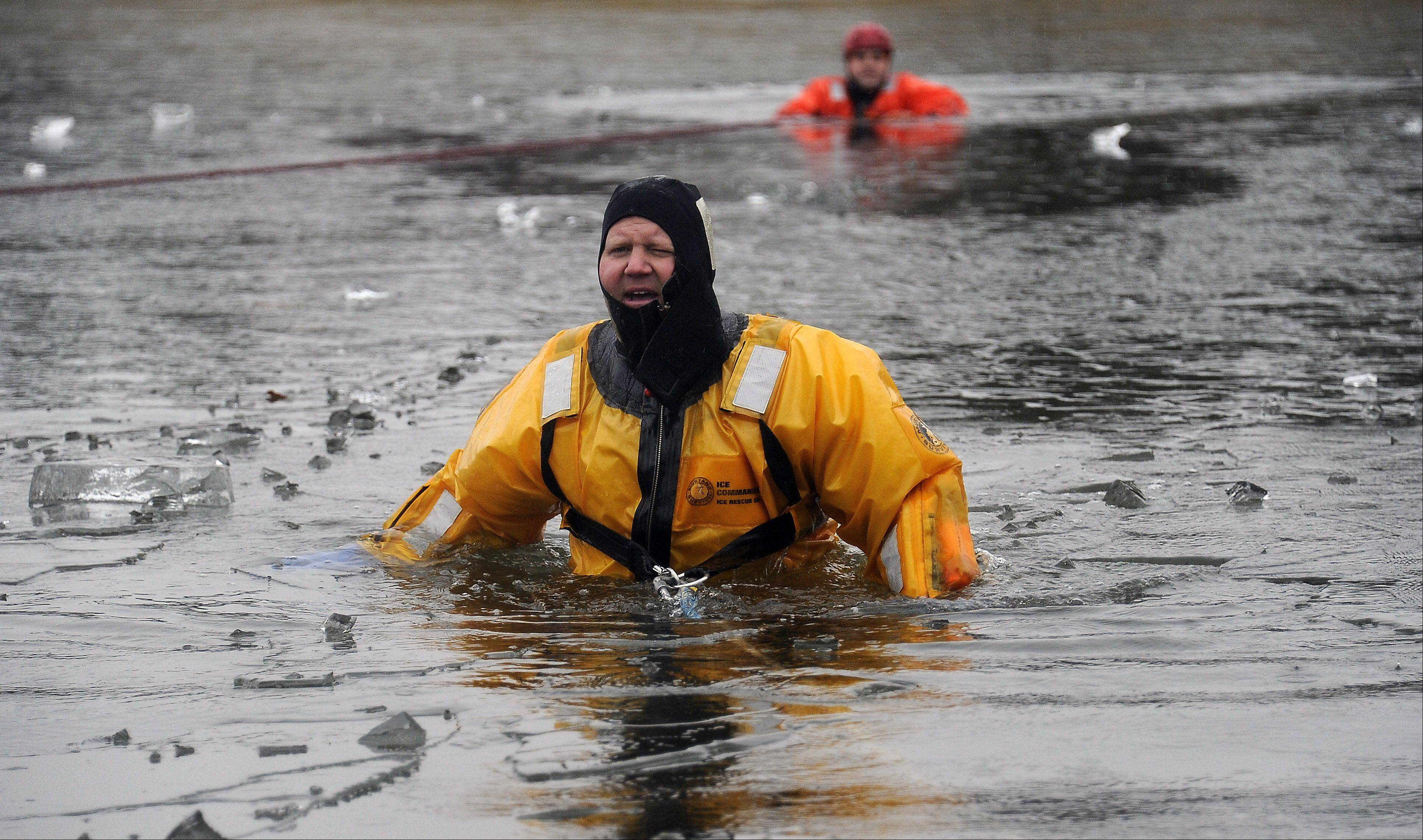 Firefighter/paramedic Jason Stockton from Lincolnshire makes ice break with his body donning a dry suit and braving the 30 degree temperature to practice his ice rescue drills. The retention pond located next to the Combined Area Fire Training Facility in Buffalo Grove is where the training took place.