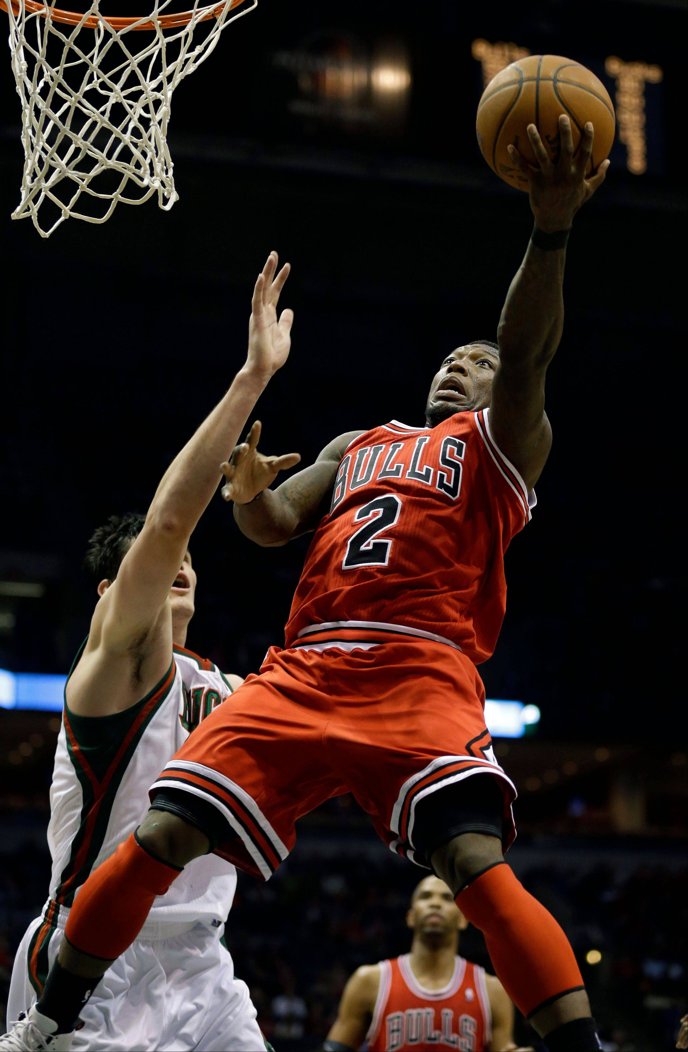 Nate Robinson (2) puts up a shot against Milwaukee�s Ersan Ilyasova, left, during the Bulls� win over the Bucks Wednesday night in Milwaukee. Robinson scored a total of 24 points during the game.