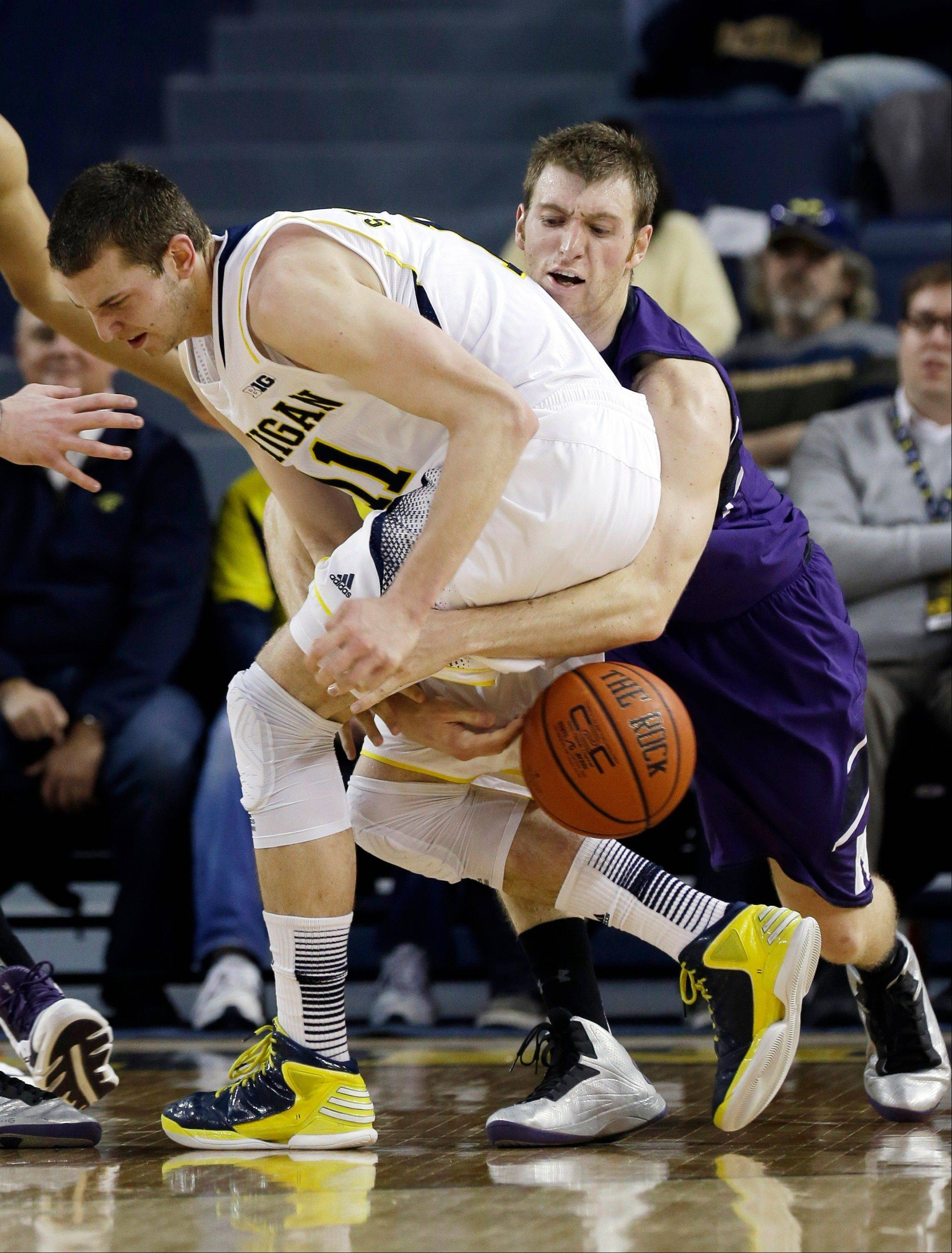 Northwestern guard Alex Marcotullio, right, reaches in on Michigan guard Nik Stauskas (11) during the Wolverines� win Wednesday night in Ann Arbor.